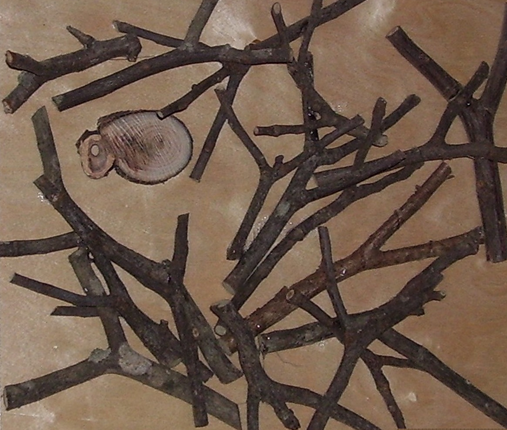 Small twigs arranged in a square with small, round piece of wood in the middle.