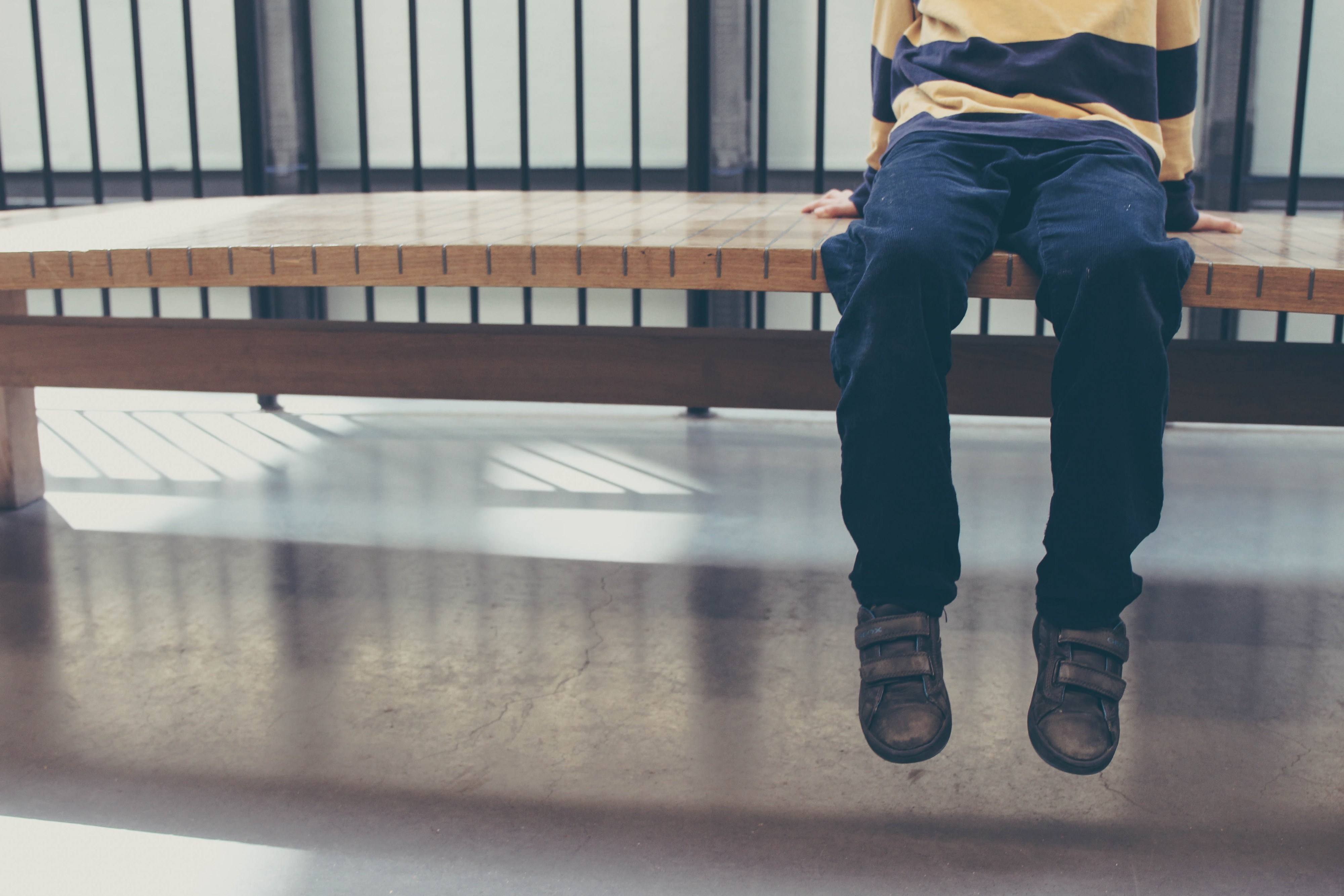 Child sitting on a bench head out of frame, with feet dangling above floor.