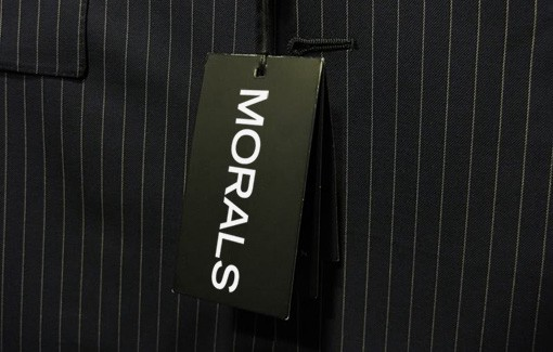"""Pinstripe suit with a label reading """"Morals"""""""