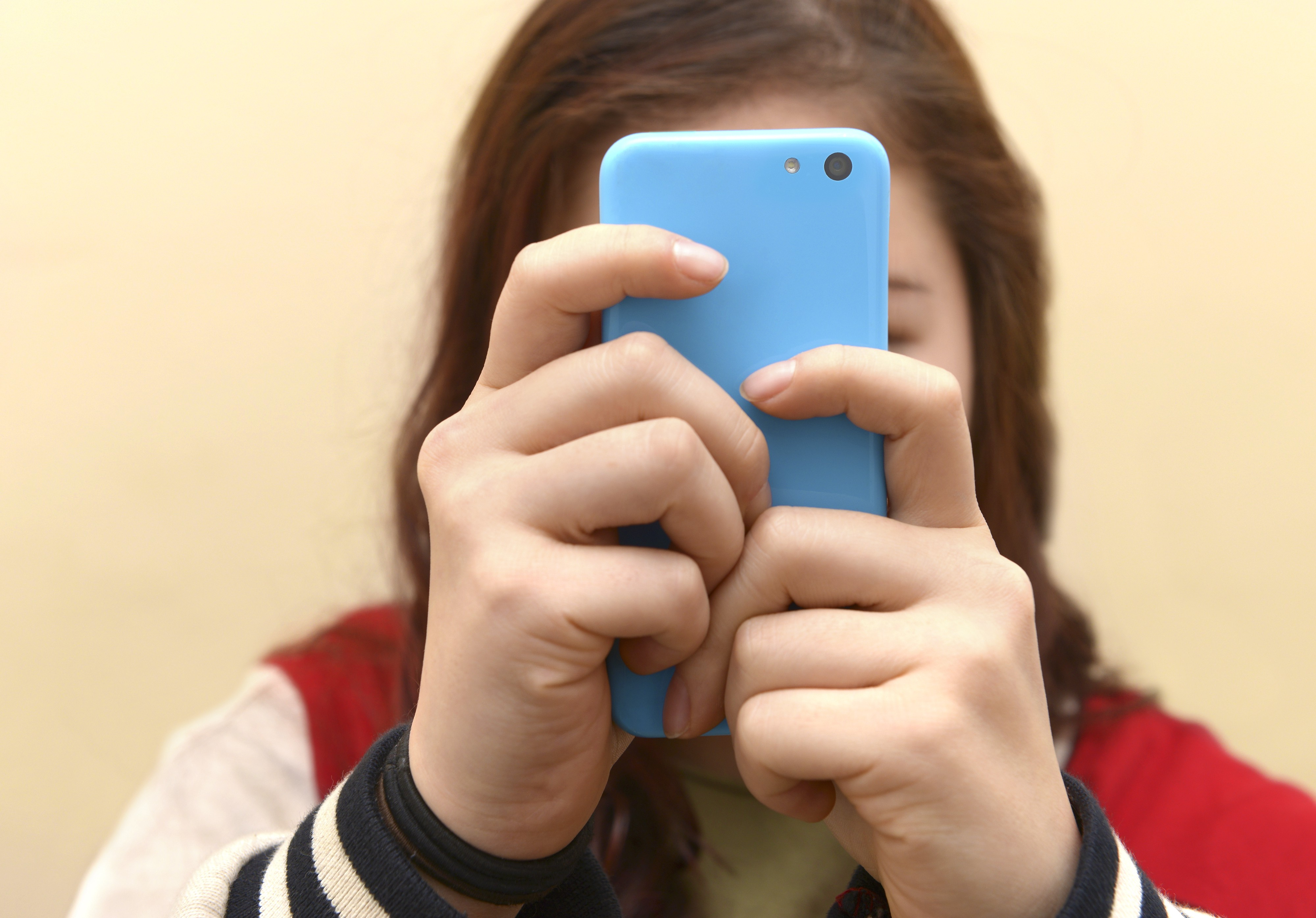 Close up of a teenager using her smartphone. Her face is obscured by her phone.
