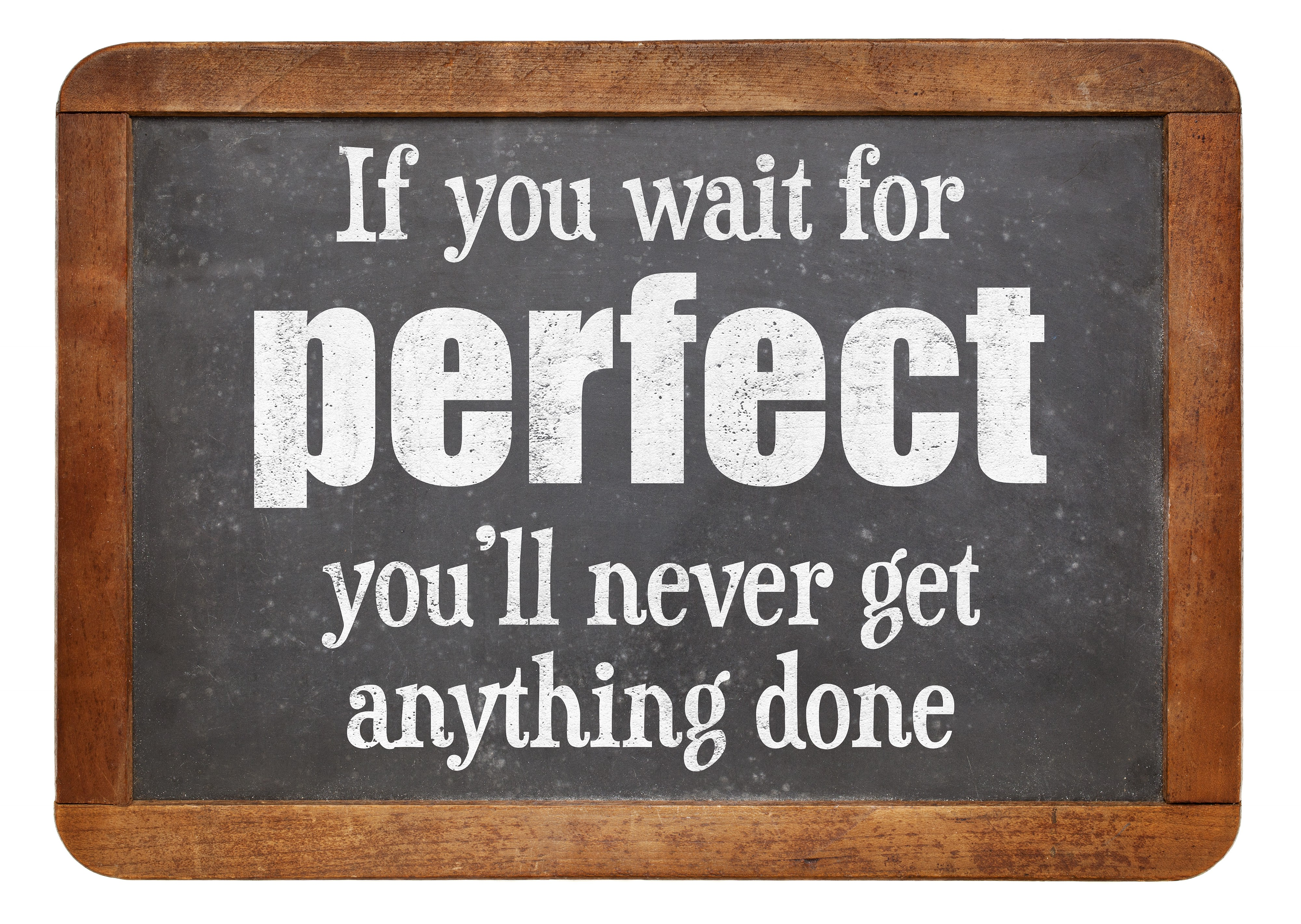 "Blackboard with wooden rim with ""If you wait for perfect, you'll never get anything done"" written in white chalk"