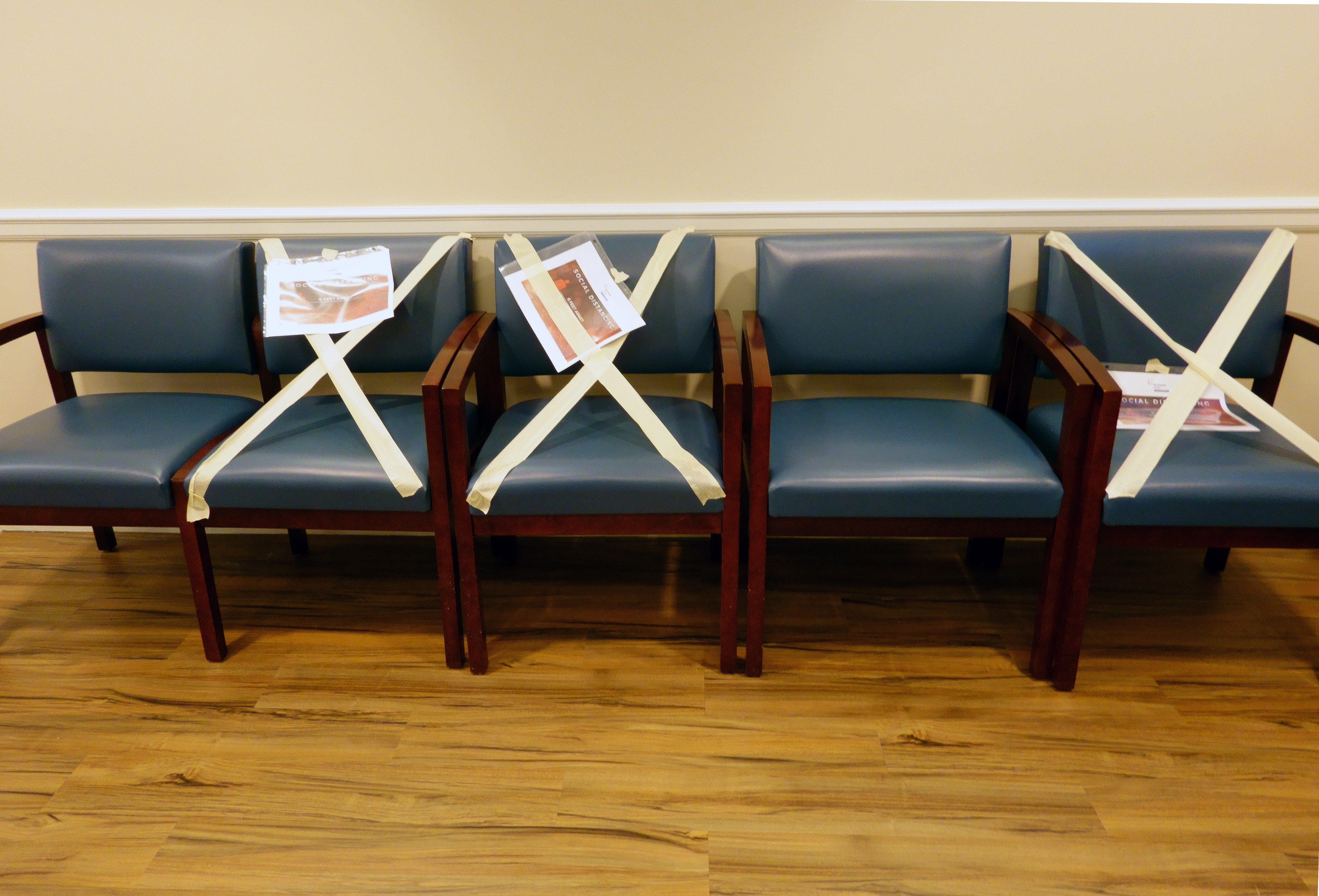 Chairs taped off in a waiting area.