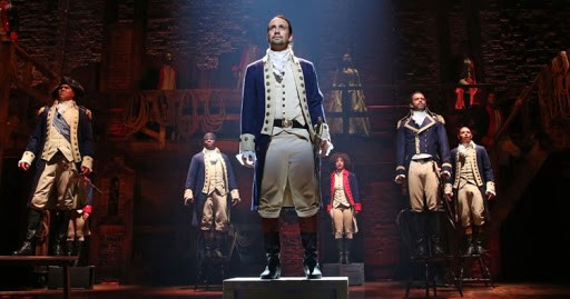 hamilton musical still with characters standing on chairs