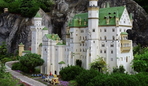 A beautifully detailed castle made out of LEGO bricks set outside in nature so that it resembles a real castle.