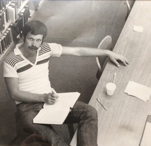 Photo of the author at age 28 sitting at a table in the law library studing