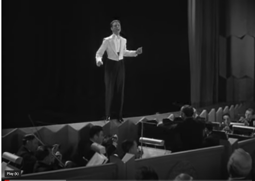 Film clip of actor in front of the orchestra pit