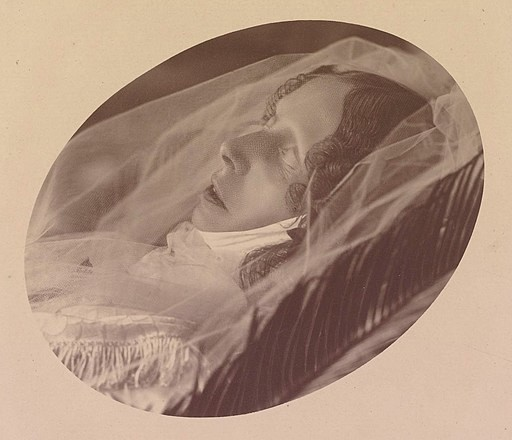 Sophie on her deathbed. Her eyes are closed and she's dressed in a white gown and veil.