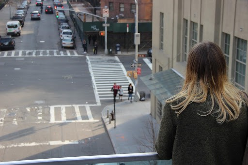 Person looking over a city street from a bridge.