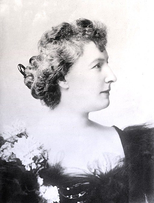 Louise in profile wearing a black ball gown and corsage. Her thick blonde hair is in a chignon.