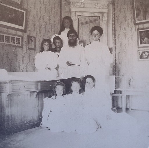 Rasputin in the royal children's nursery, surrounded by all 5 royal kids, Empress Alexandra, and their governess.