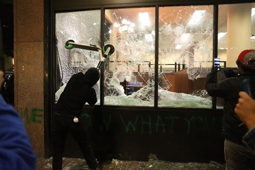 A rioter breaking a store window with a scooter