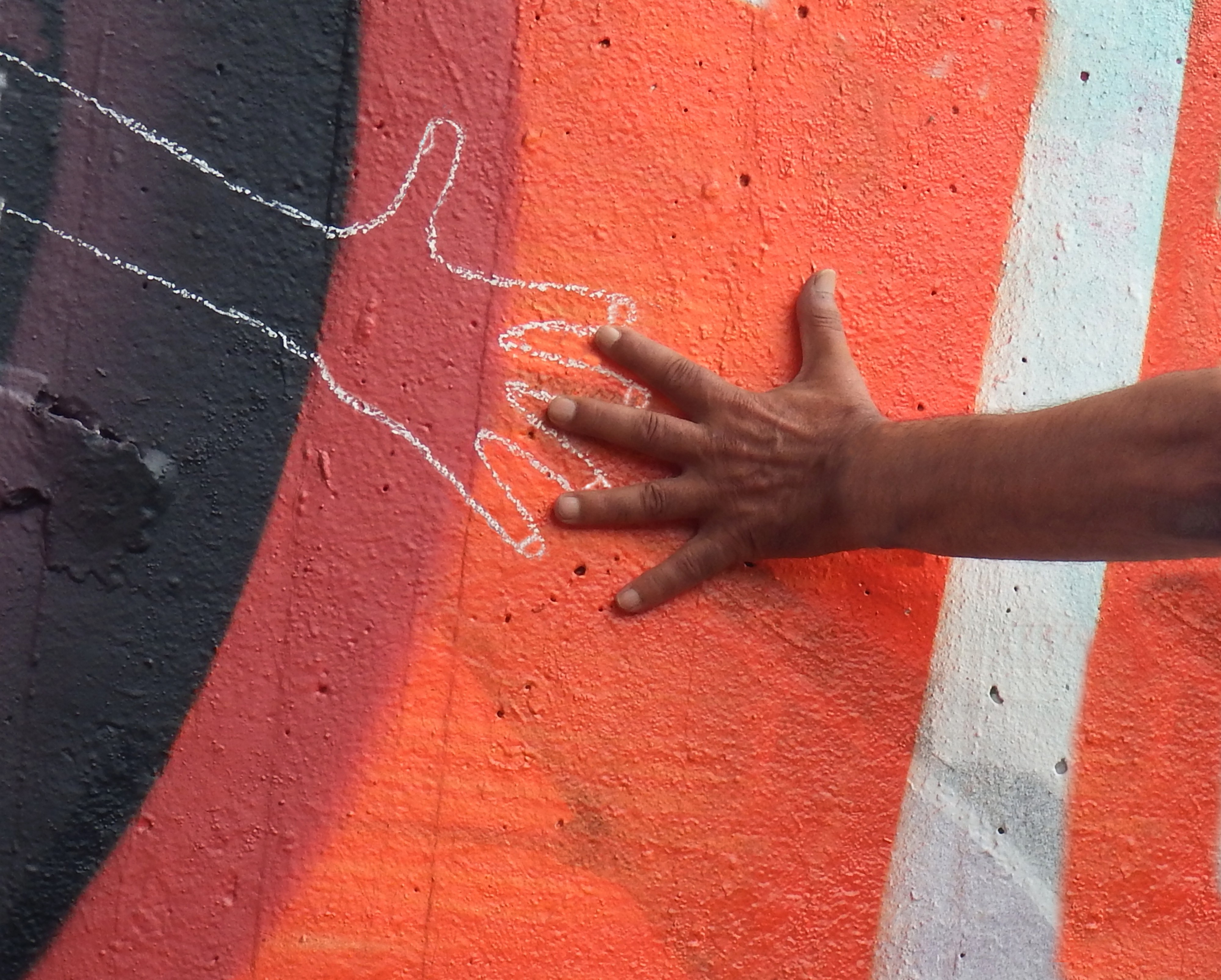 One hand holding the chalk outline of another hand on a wall.