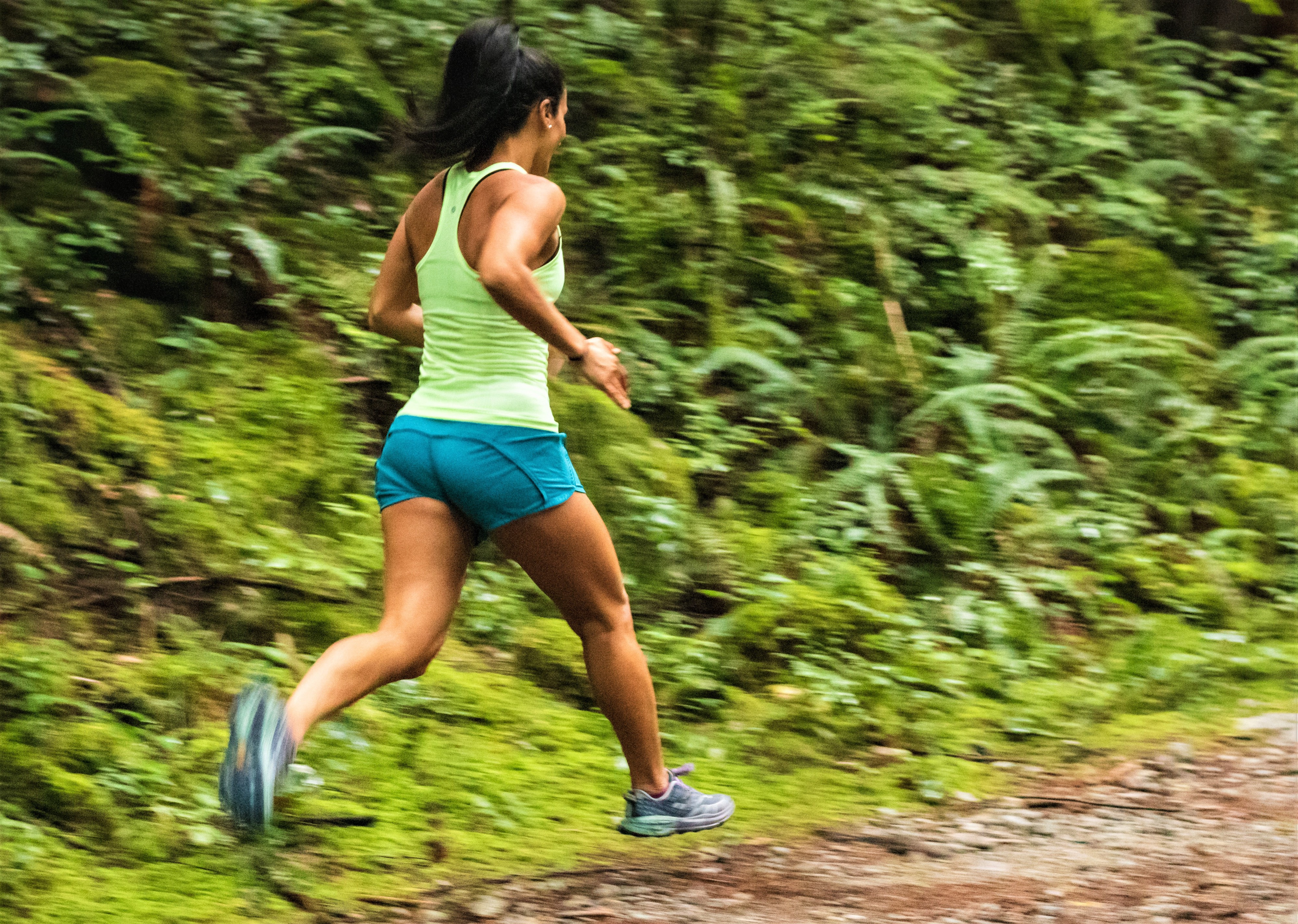 girl with brown hair wearing green t-shirt and blue shorts running on path in forest