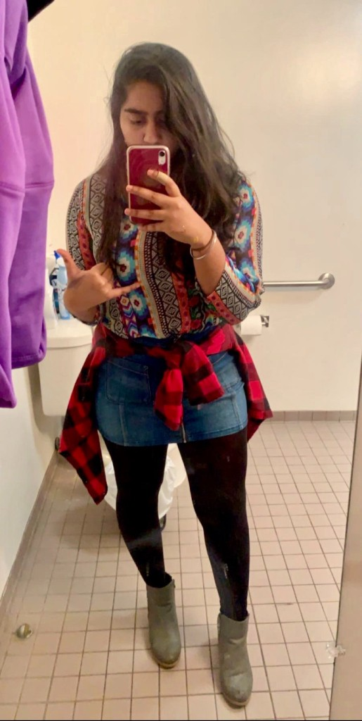 Indian girl wears a bright patterned shirt with denim skirt in a bathroom