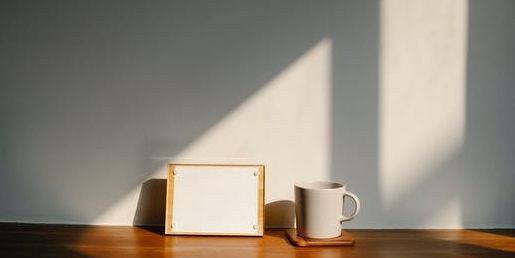 Blank paper on an easel. Coffee mug next to it. Reflection of sun from a nearby window on the wall casting a shadow on the wall and desktop.