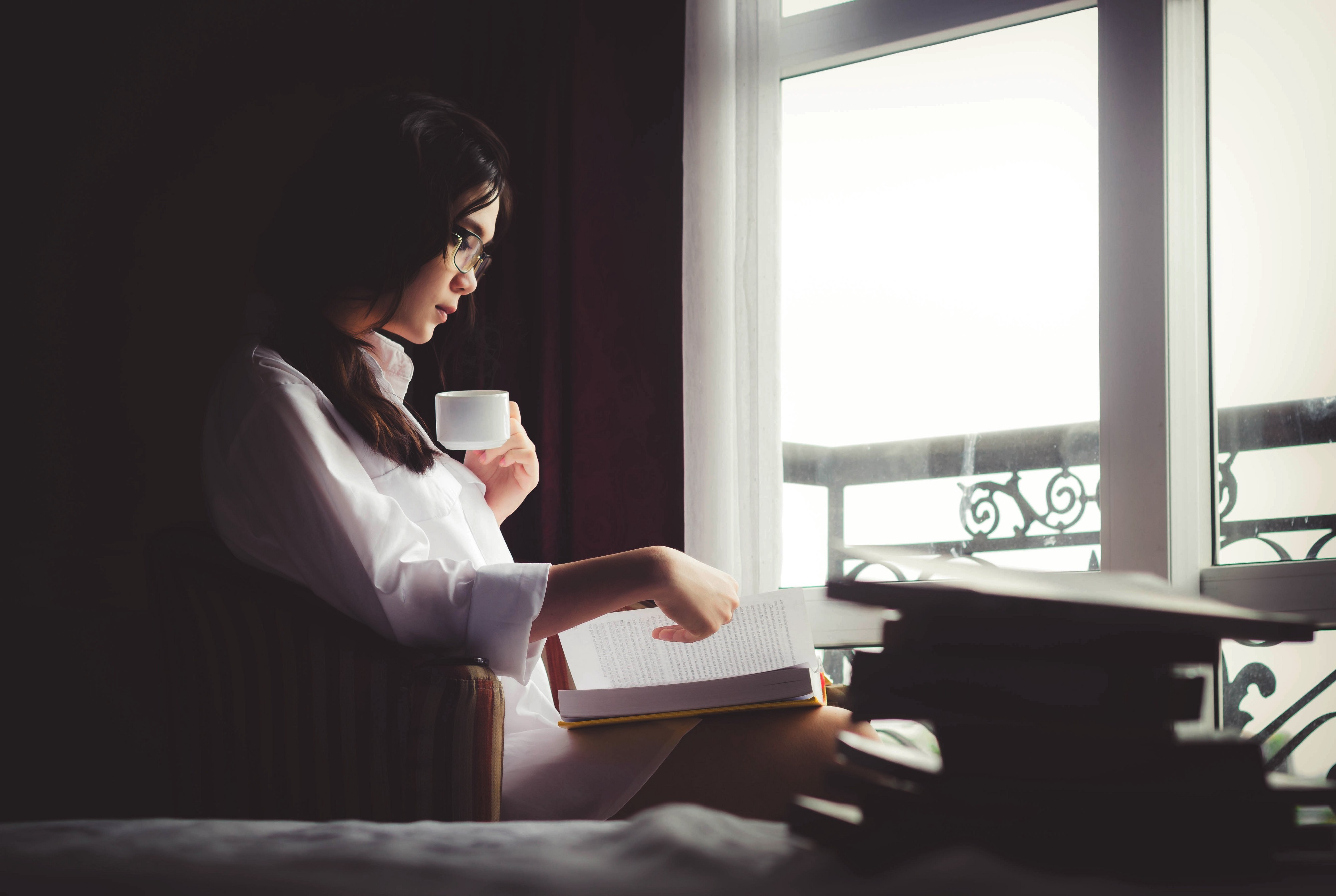 A woman drinking a cup of coffee while reading a book by a window.