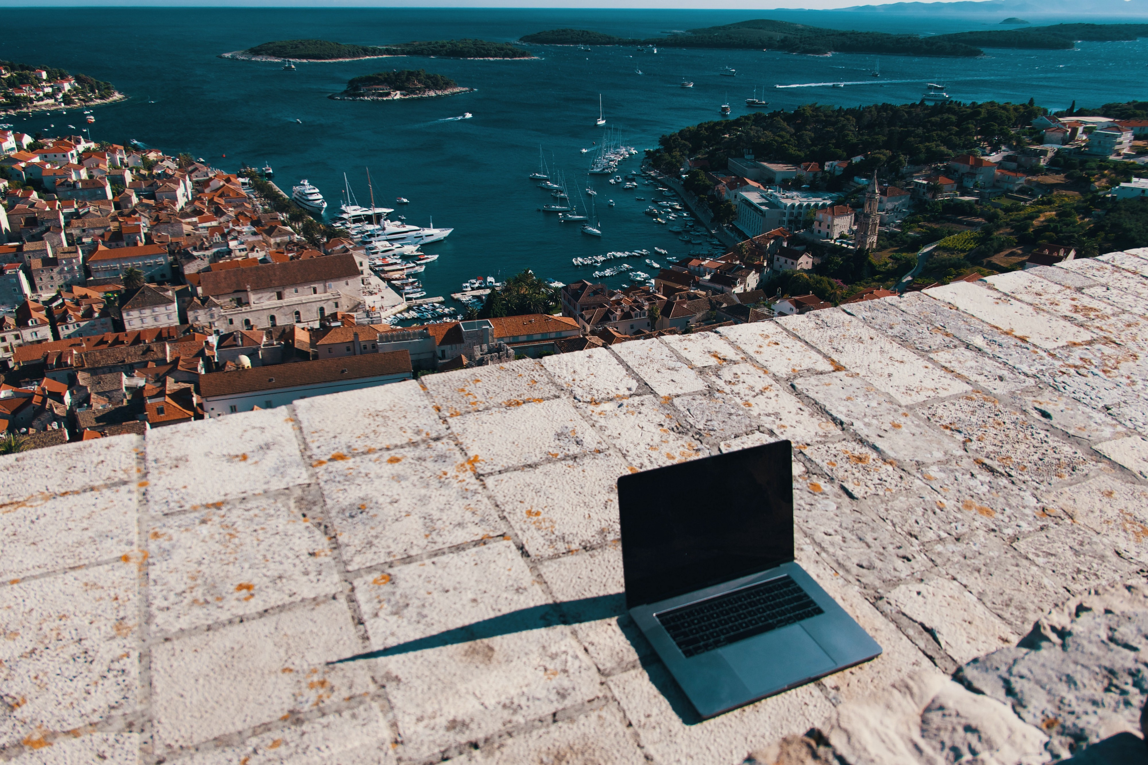 Laptop on brick wall with view of ocean and town behind it.