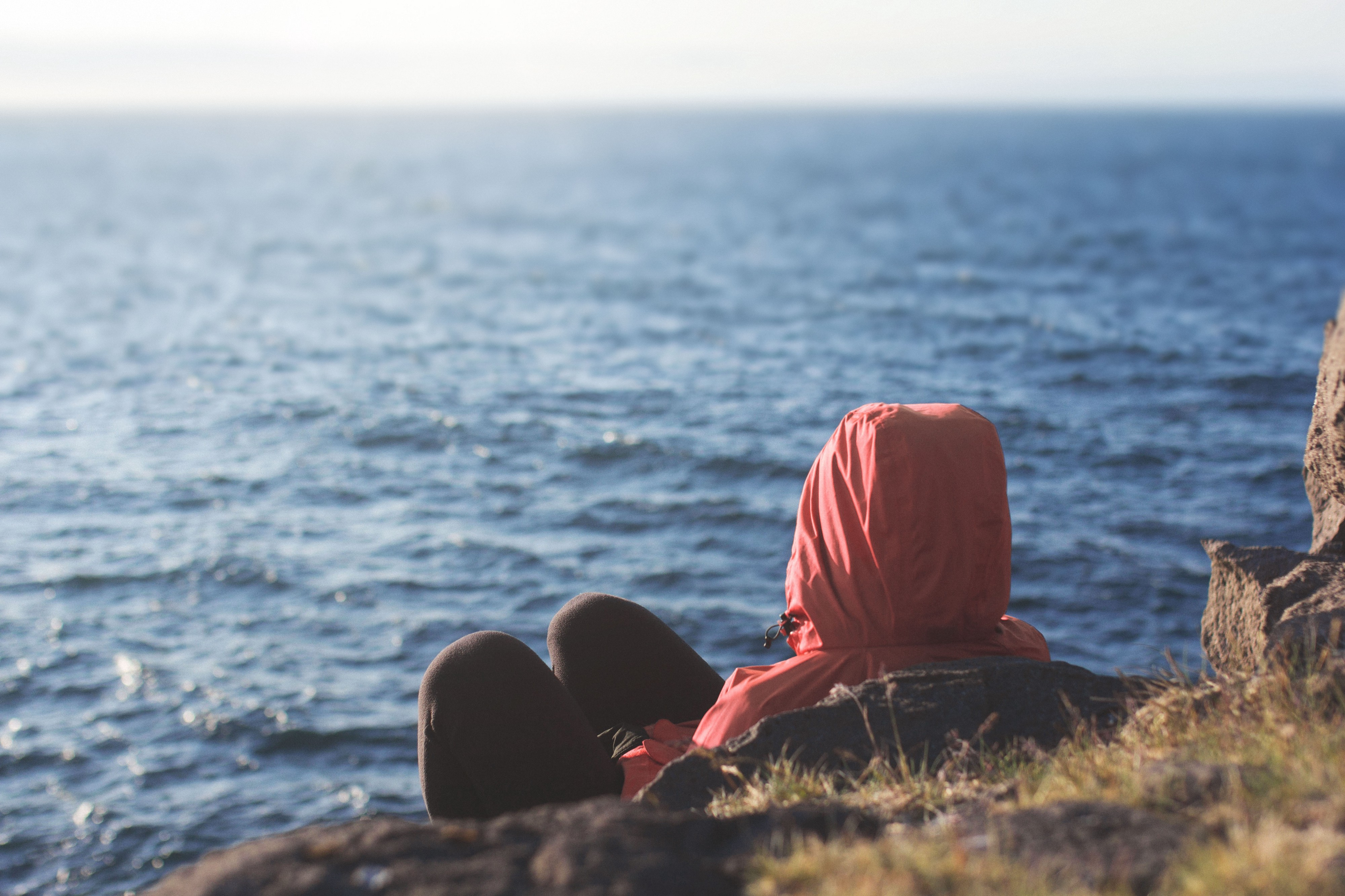 Photo of a person wearing a hoodie leaning on some rocks at the beach and looking out at the ocean
