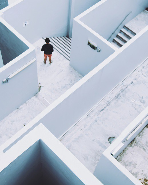Aerial view of person in a maze-like building at the top of a staircase