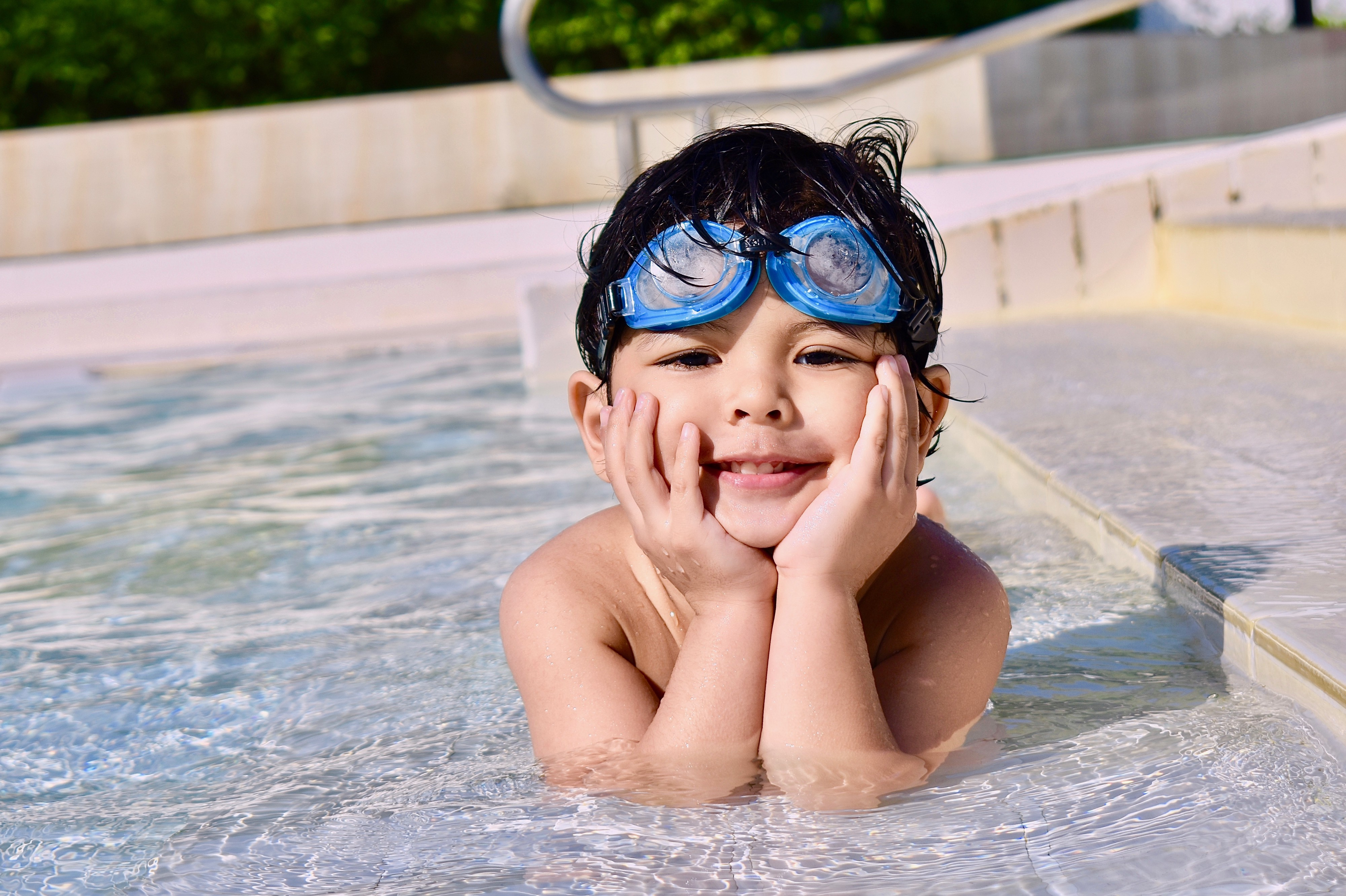 A handsome child sun bathing in the pool with his hands touching his face