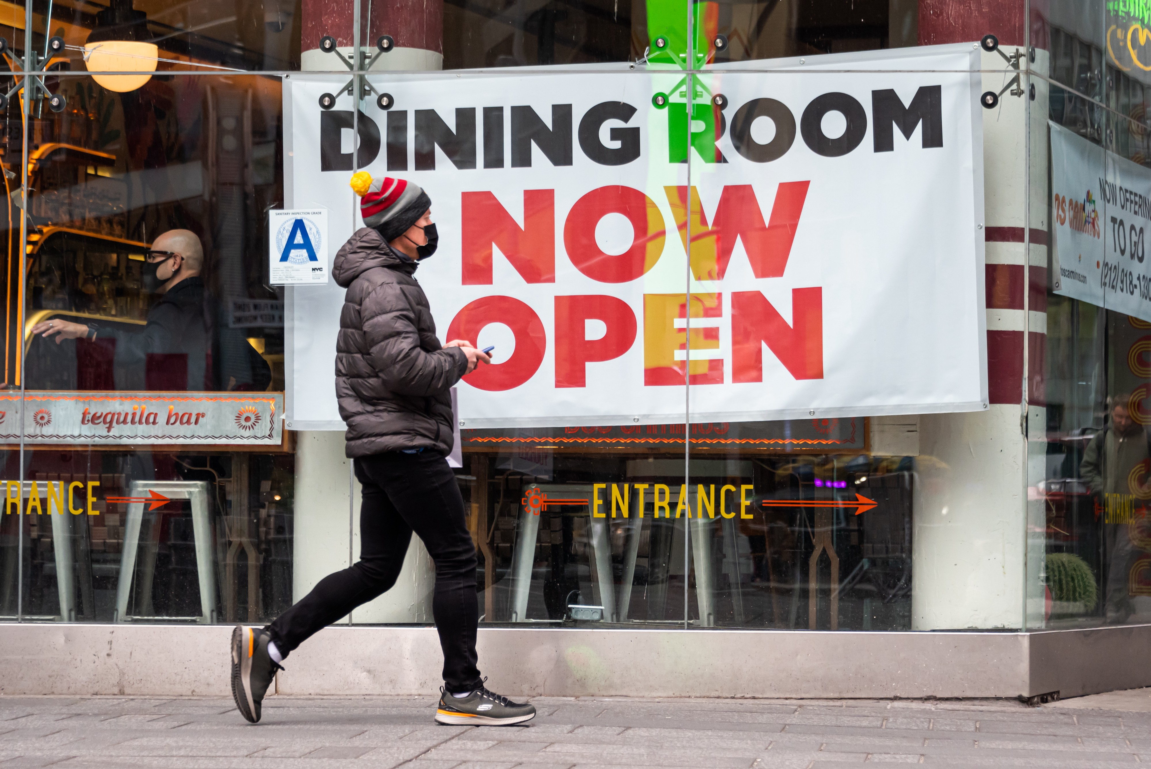 """A person walks by a sign that reads, """"Dining room now open"""" outside a restaurant in Times Square."""