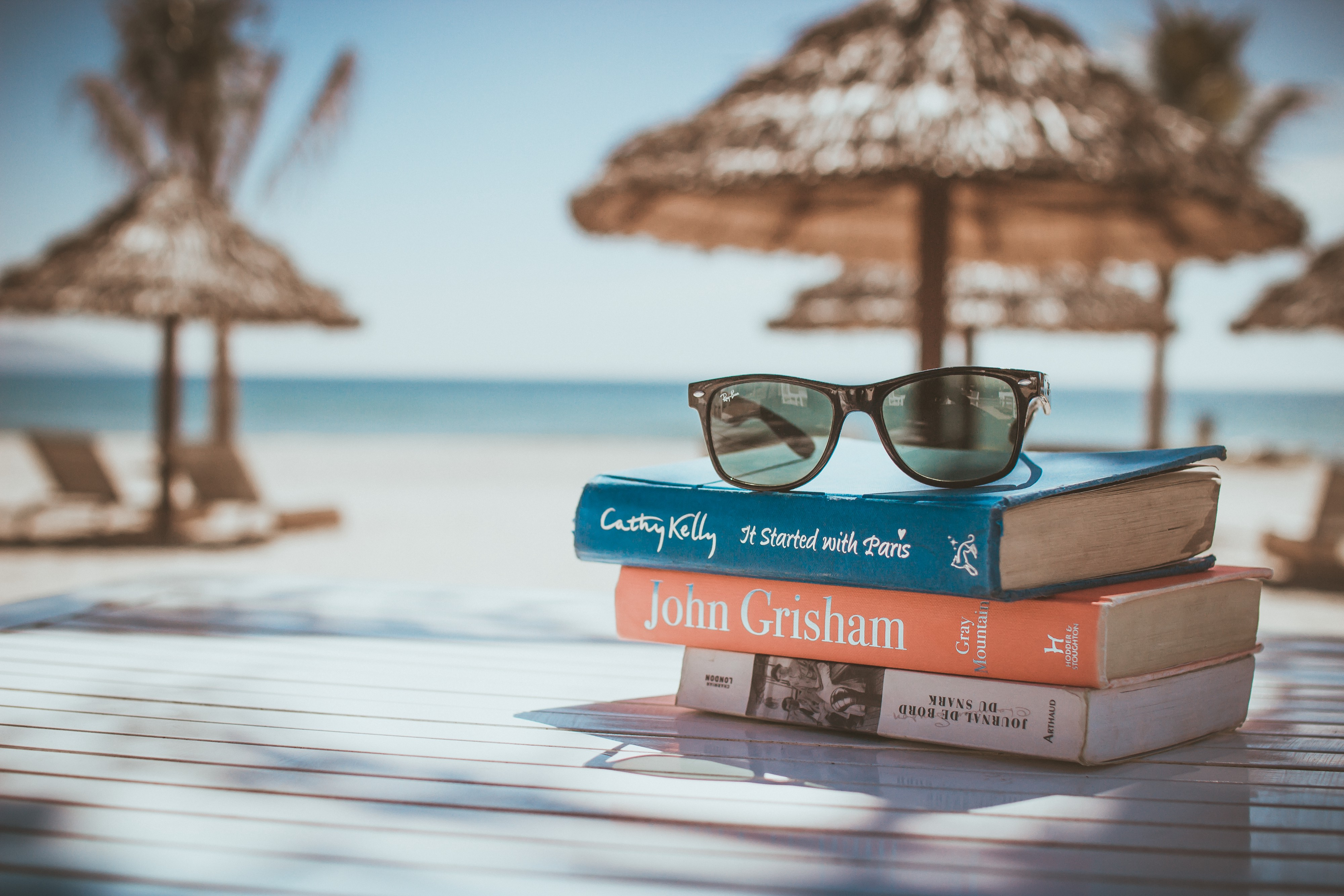stack of books on beach with sunglasses and beach umbrella