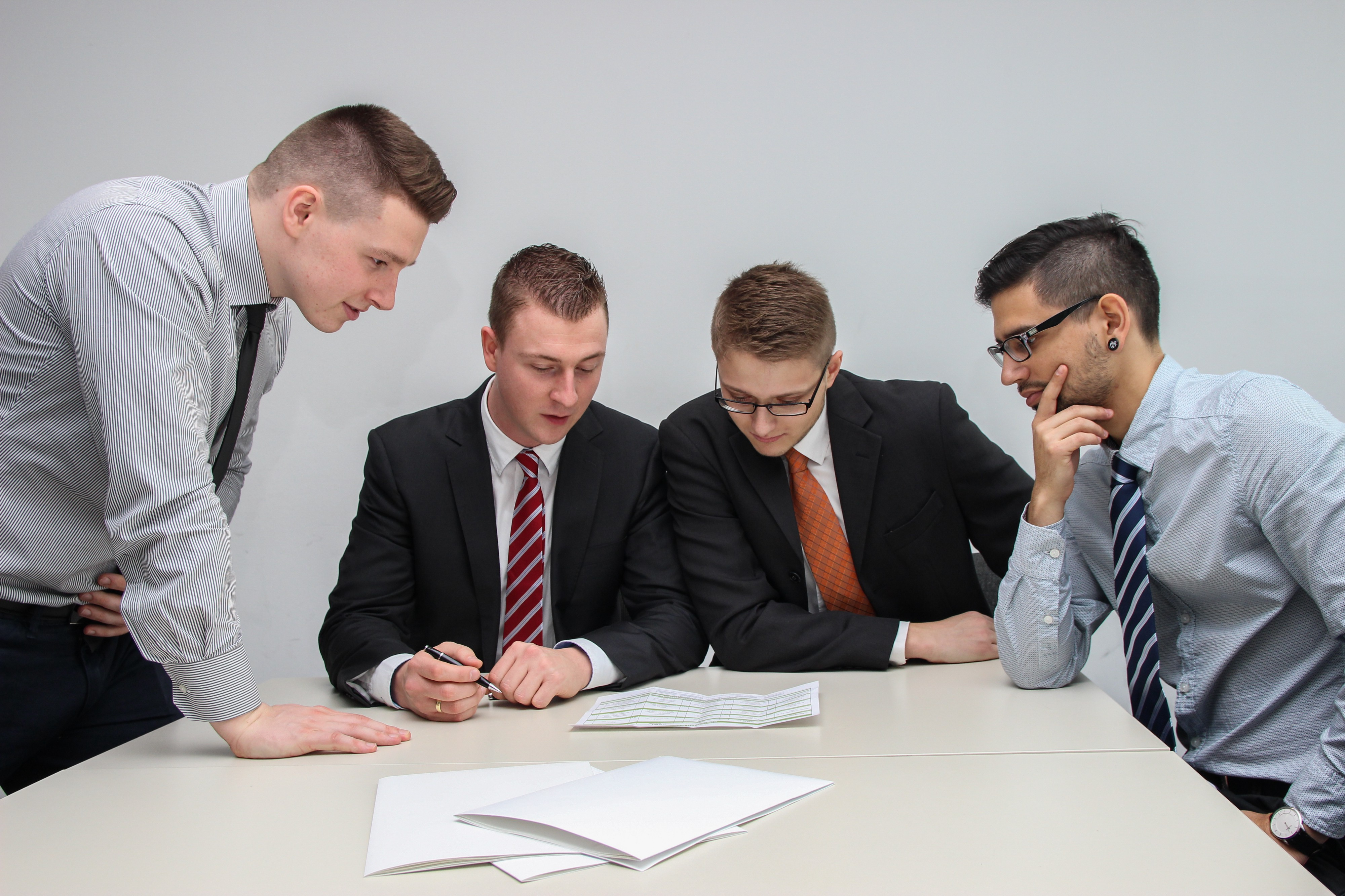 four men in suits and ties looking at documents on a desk