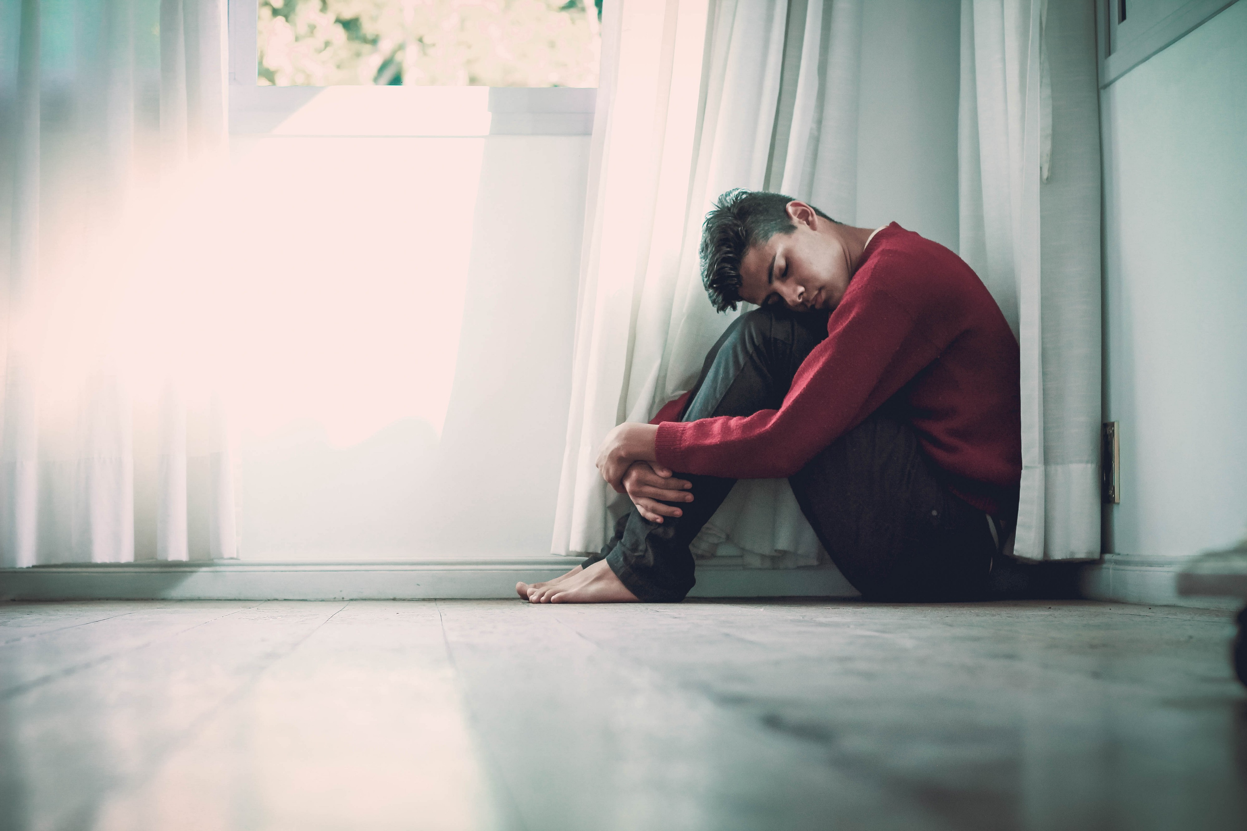young man hunched on the floor feeling depressed.