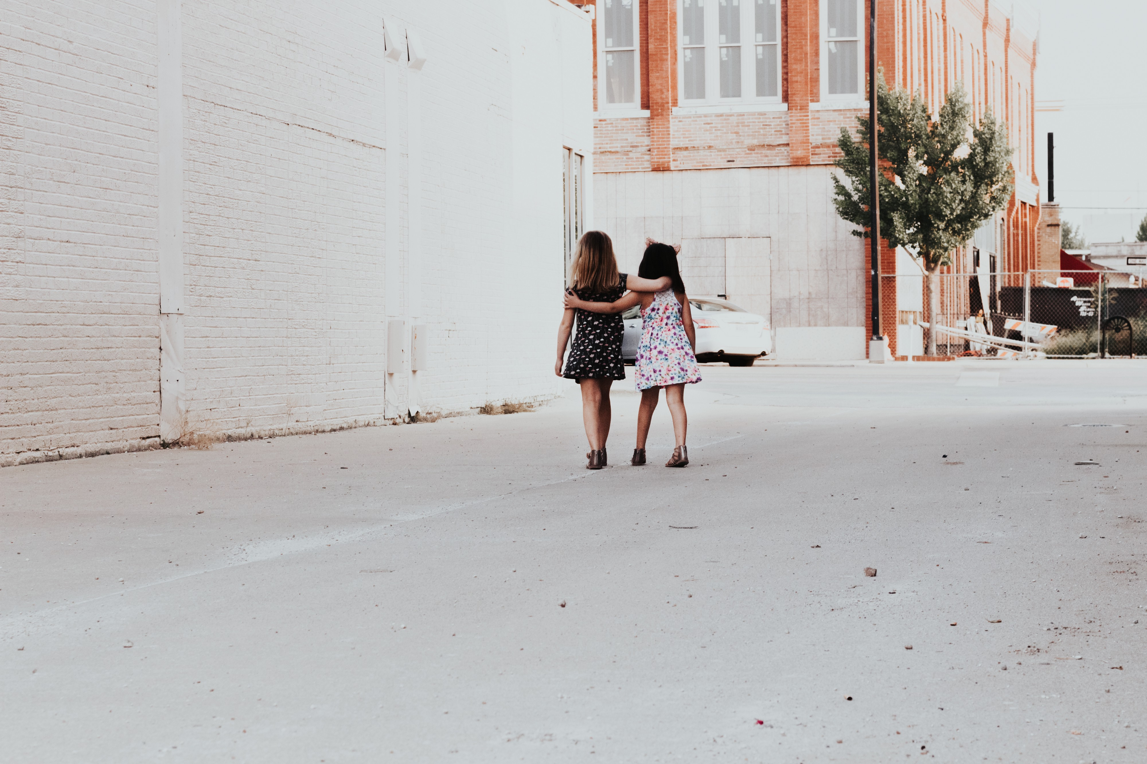 Two little girls in cute dresses walk arm and arm down a city alley.