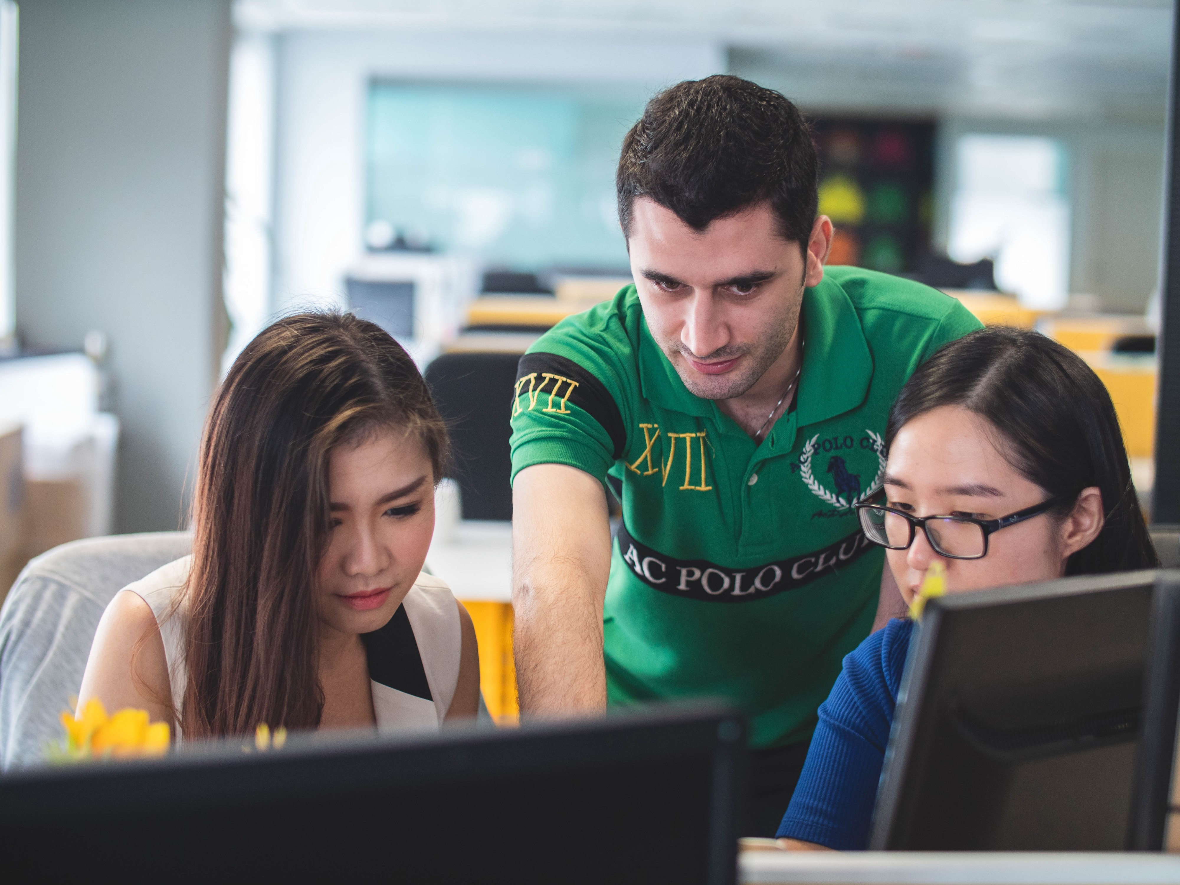 A man explaining something to two Asian girls in front of a computer