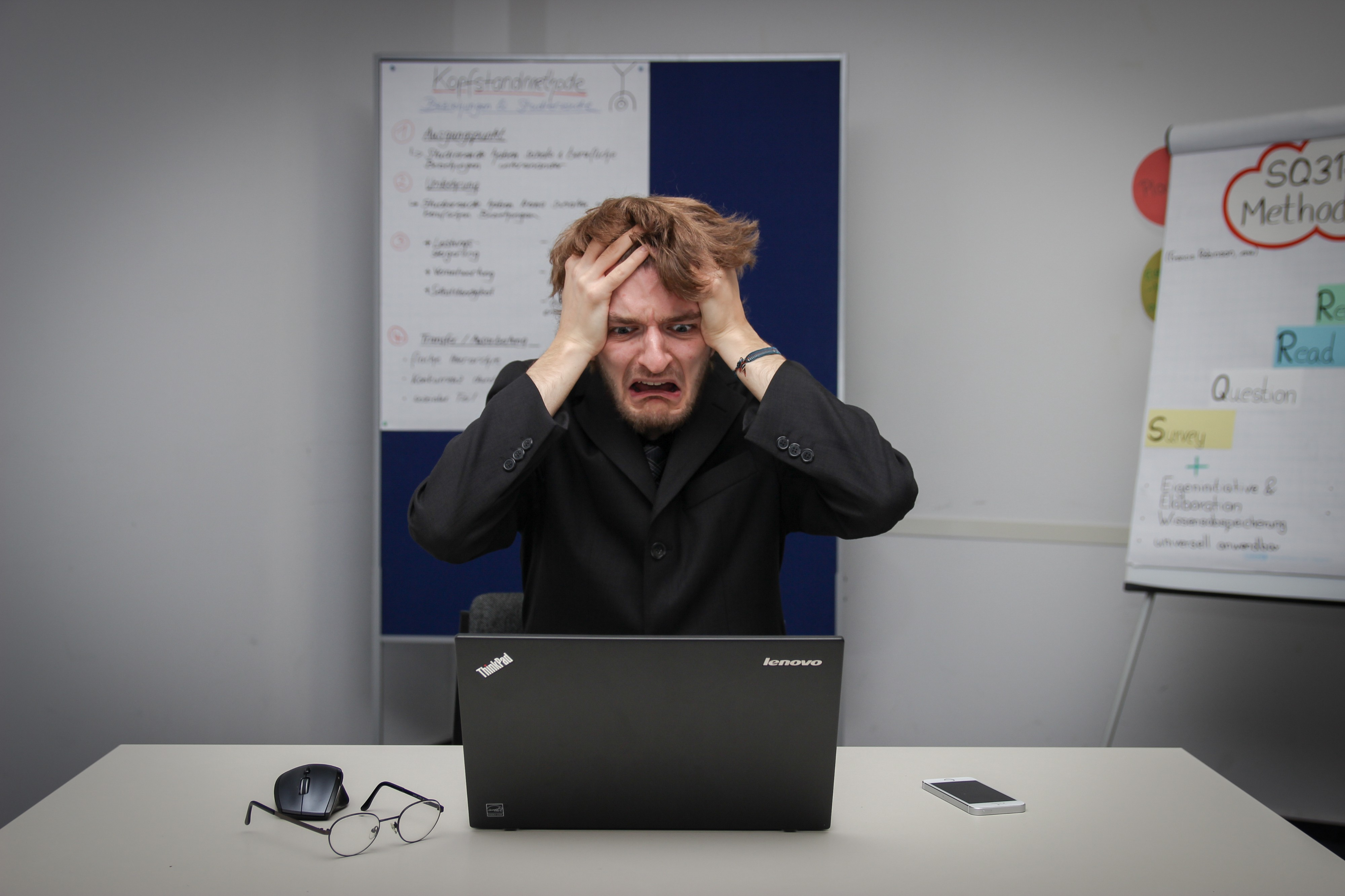 A man in a black suit looks at his laptop in pure frustration.