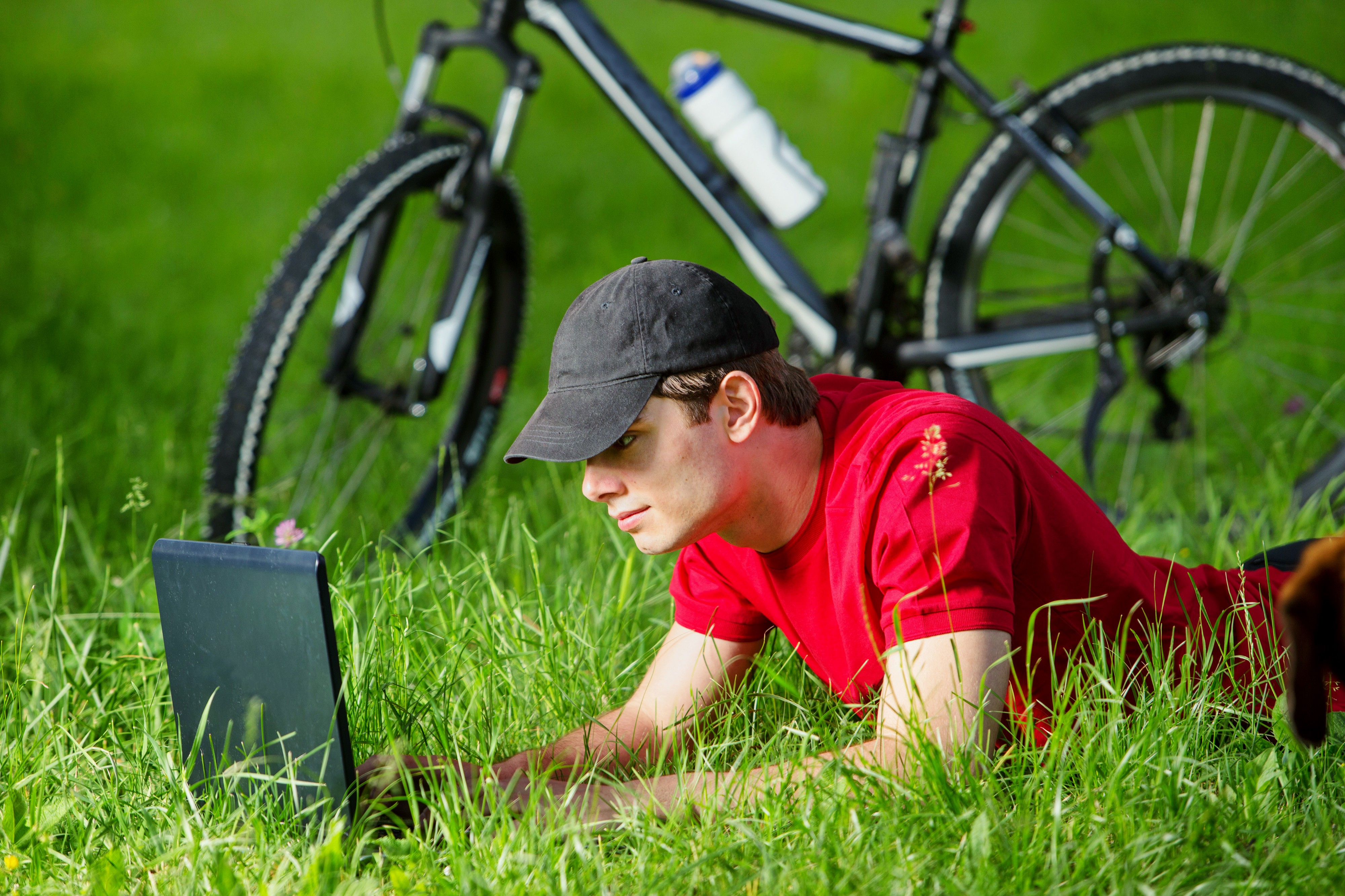 A young guy in a red t-shirt and black ball cap laying on his belly in the grass using a laptop—his ten speed bicycle in the background