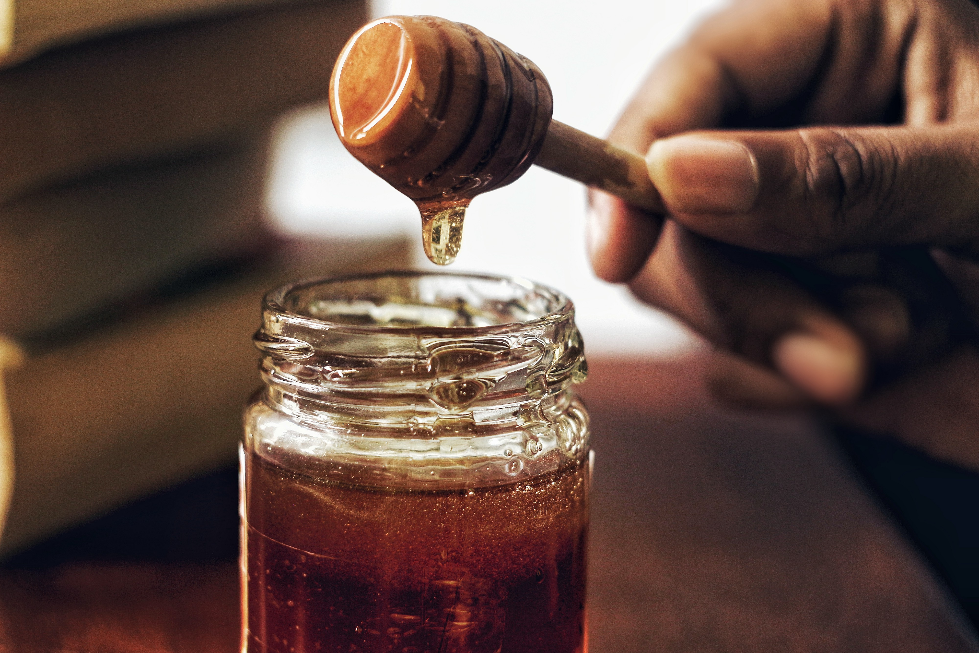 honey dripping from a wooden utensil held between fingers