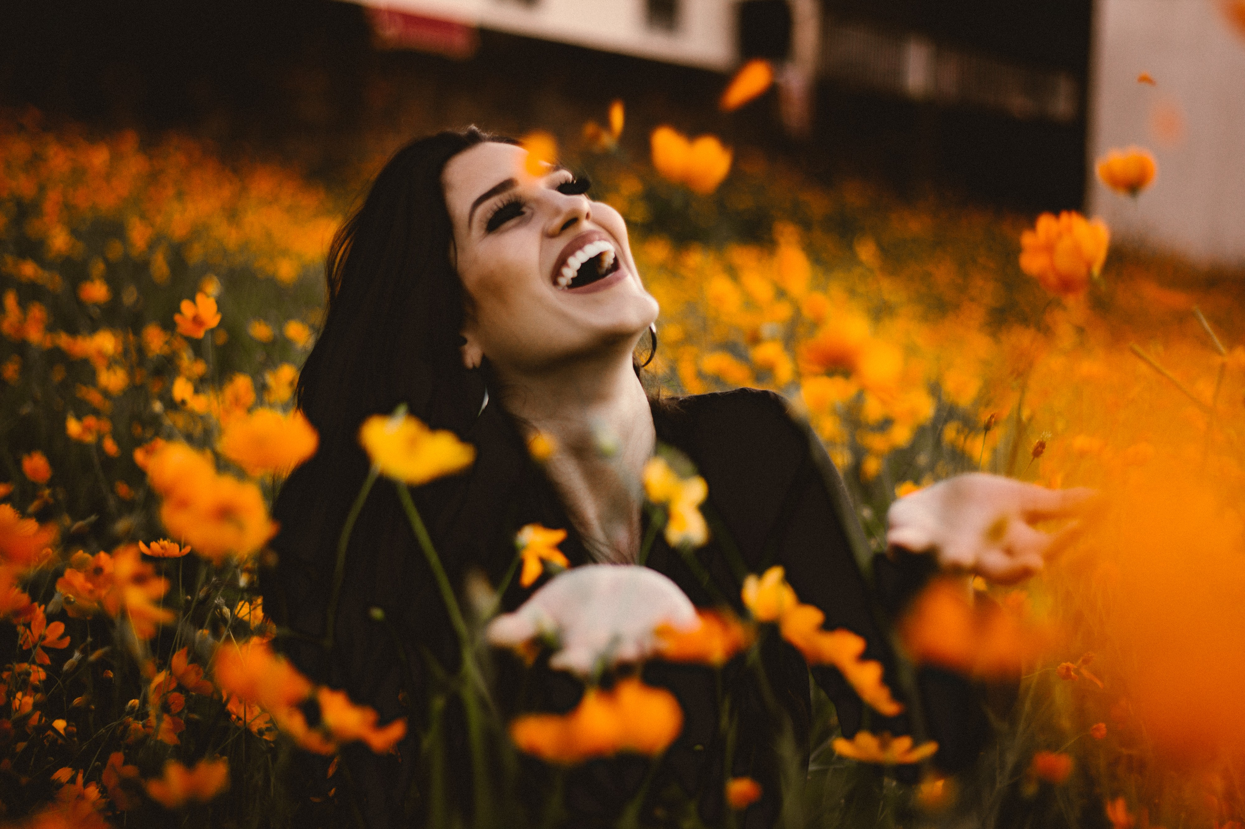 Smiling women wearing light makeup, golden ear loops and black shirt in field of orange flowers with open palms pointing upwards, looking up. She seems content about life.