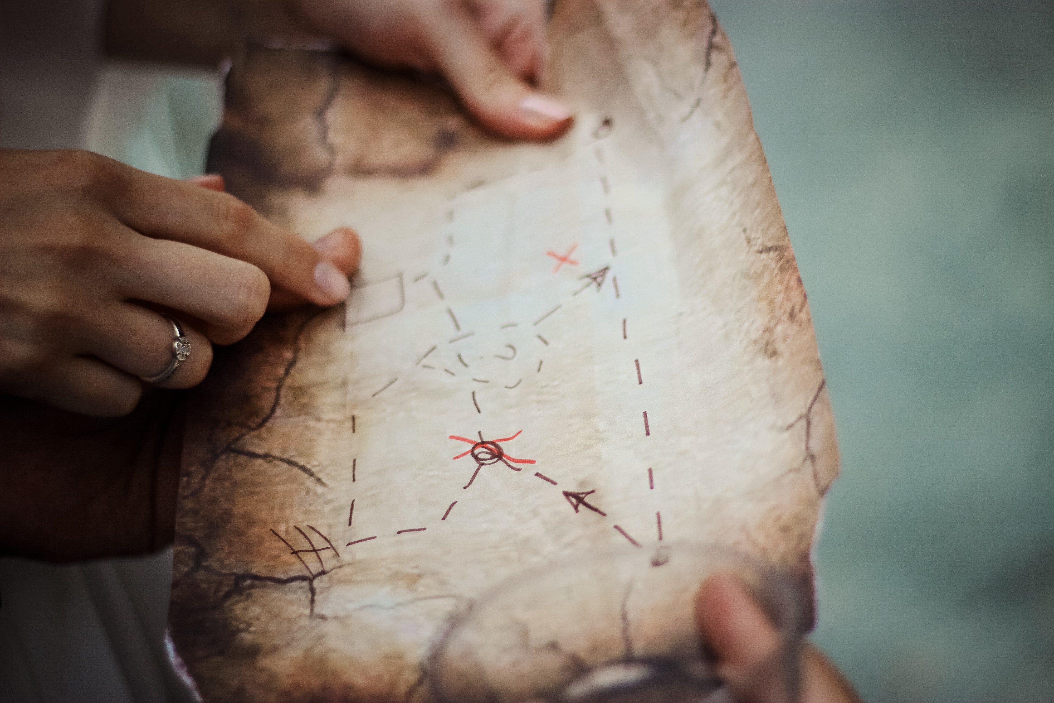 """A old """"treasure map"""" with hands holding it and pointing at it."""