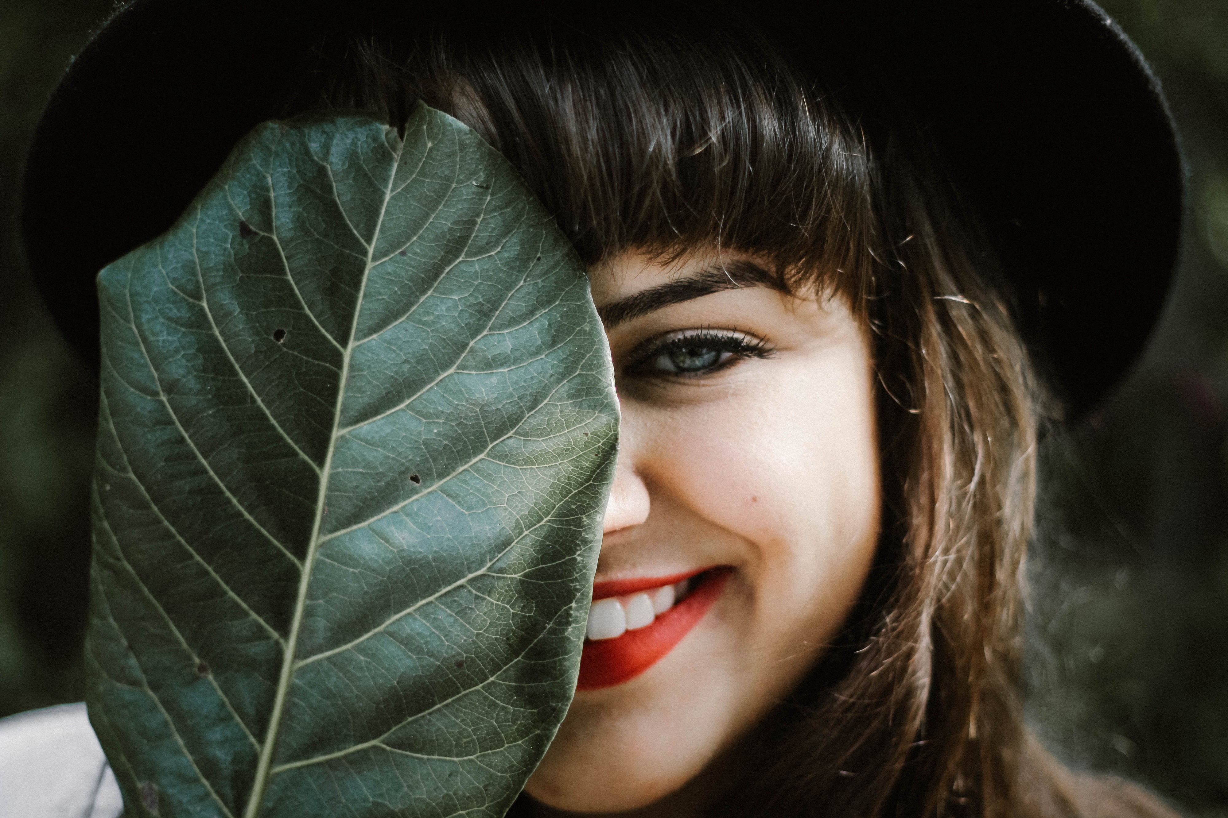 A beautiful girl smiling with half of her face playfully hidden behind a leaf. She has red lipstick and a black hat on.