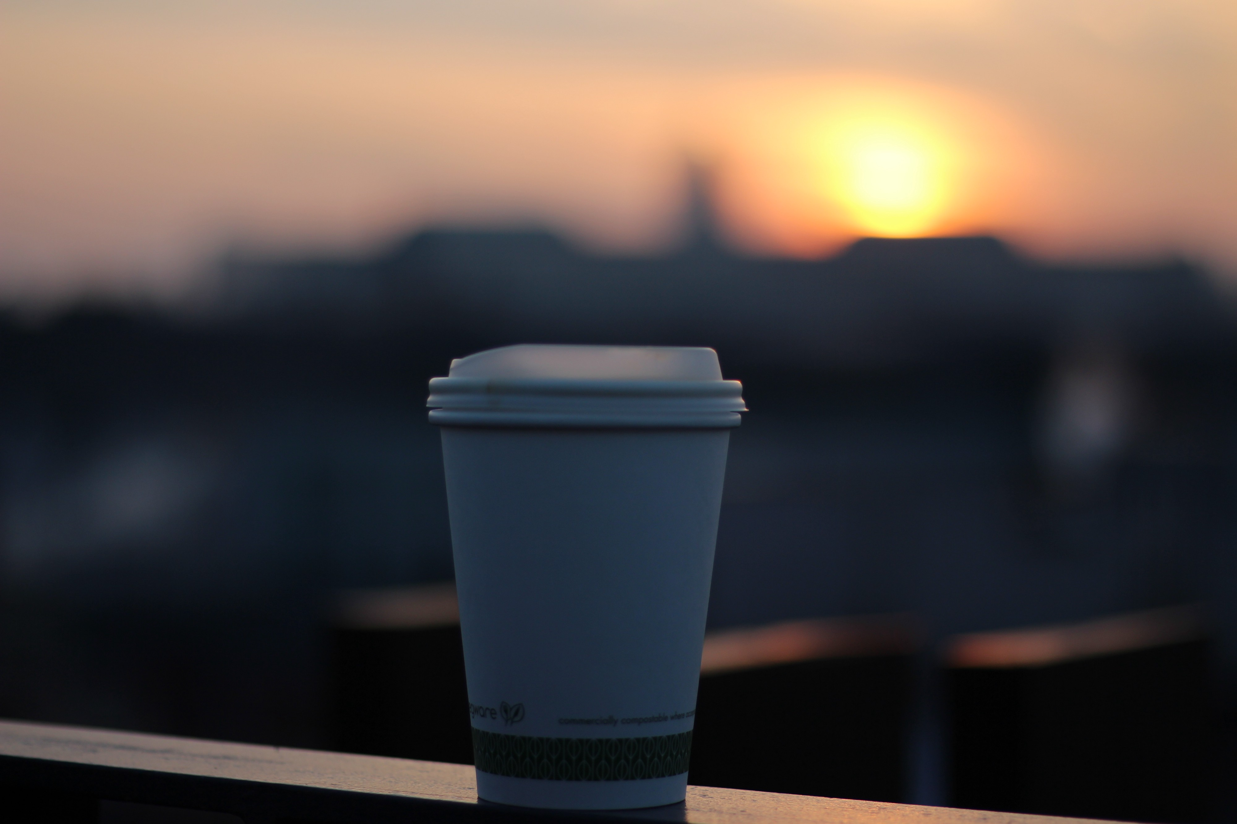 A reusable coffee cup on a ledge with the sun setting over a city in the background