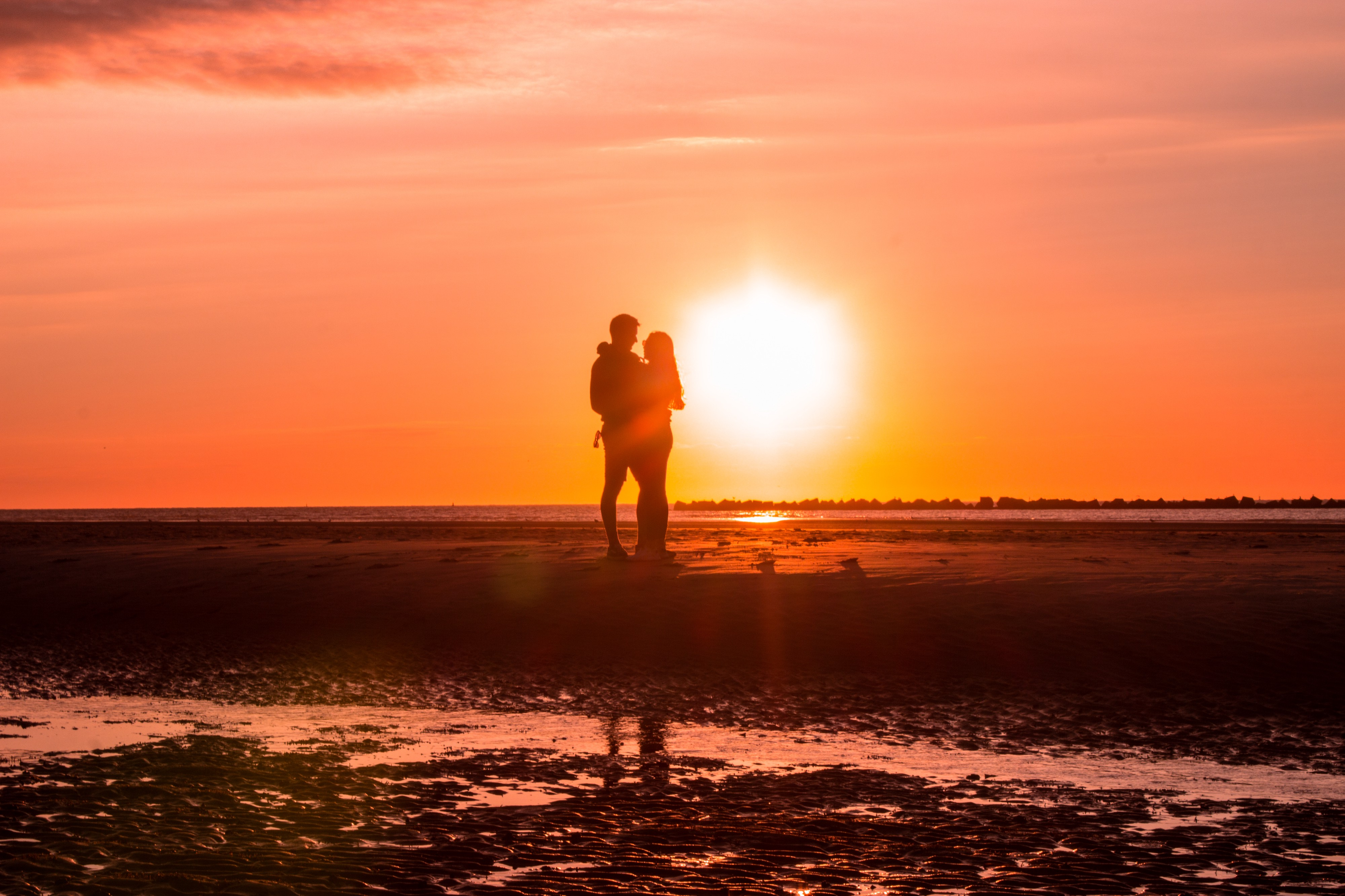 Lovers embracing on the shore as the sun sets and the waves hug their legs.