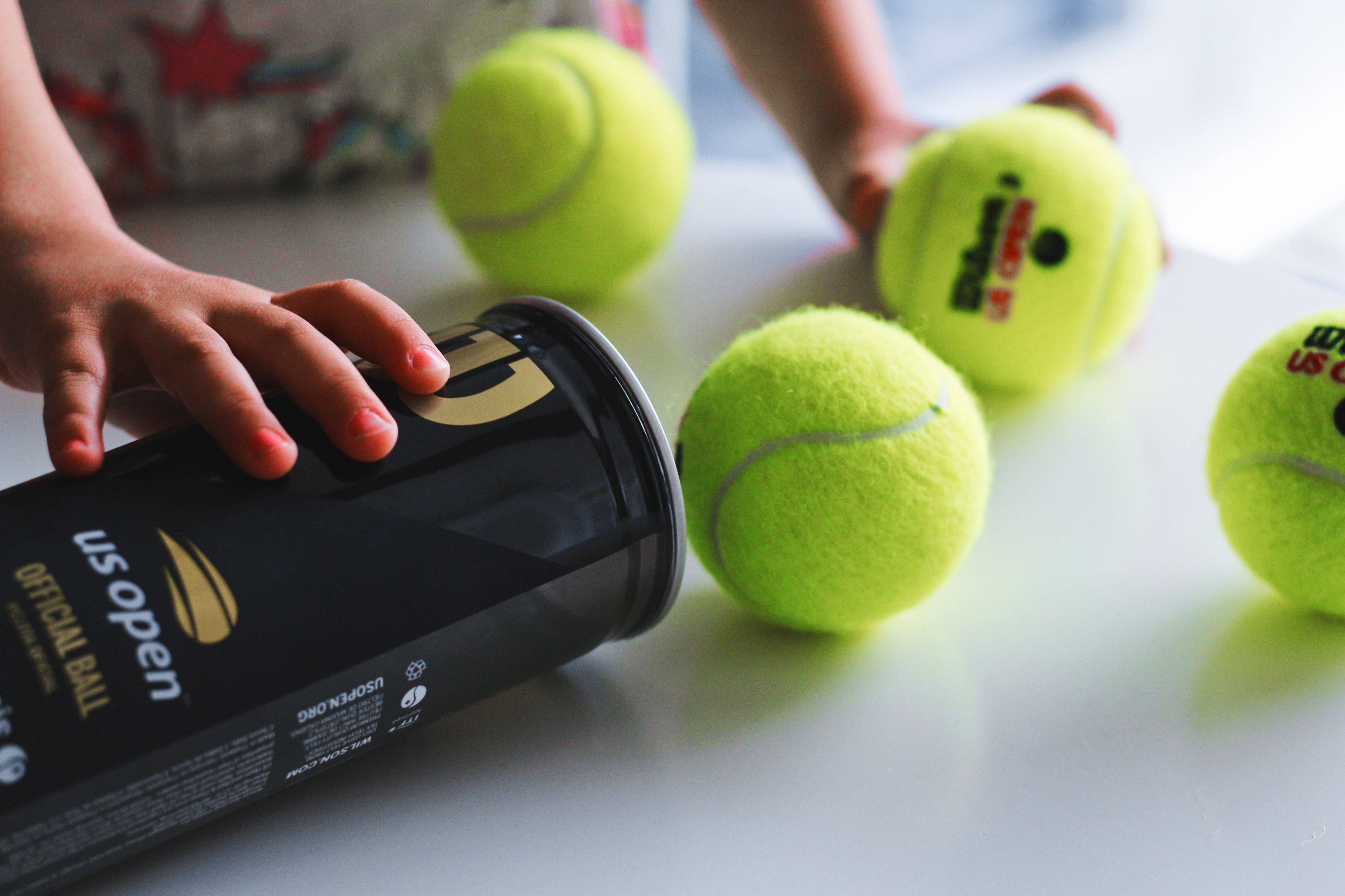 Person getting tennis balls out of the can