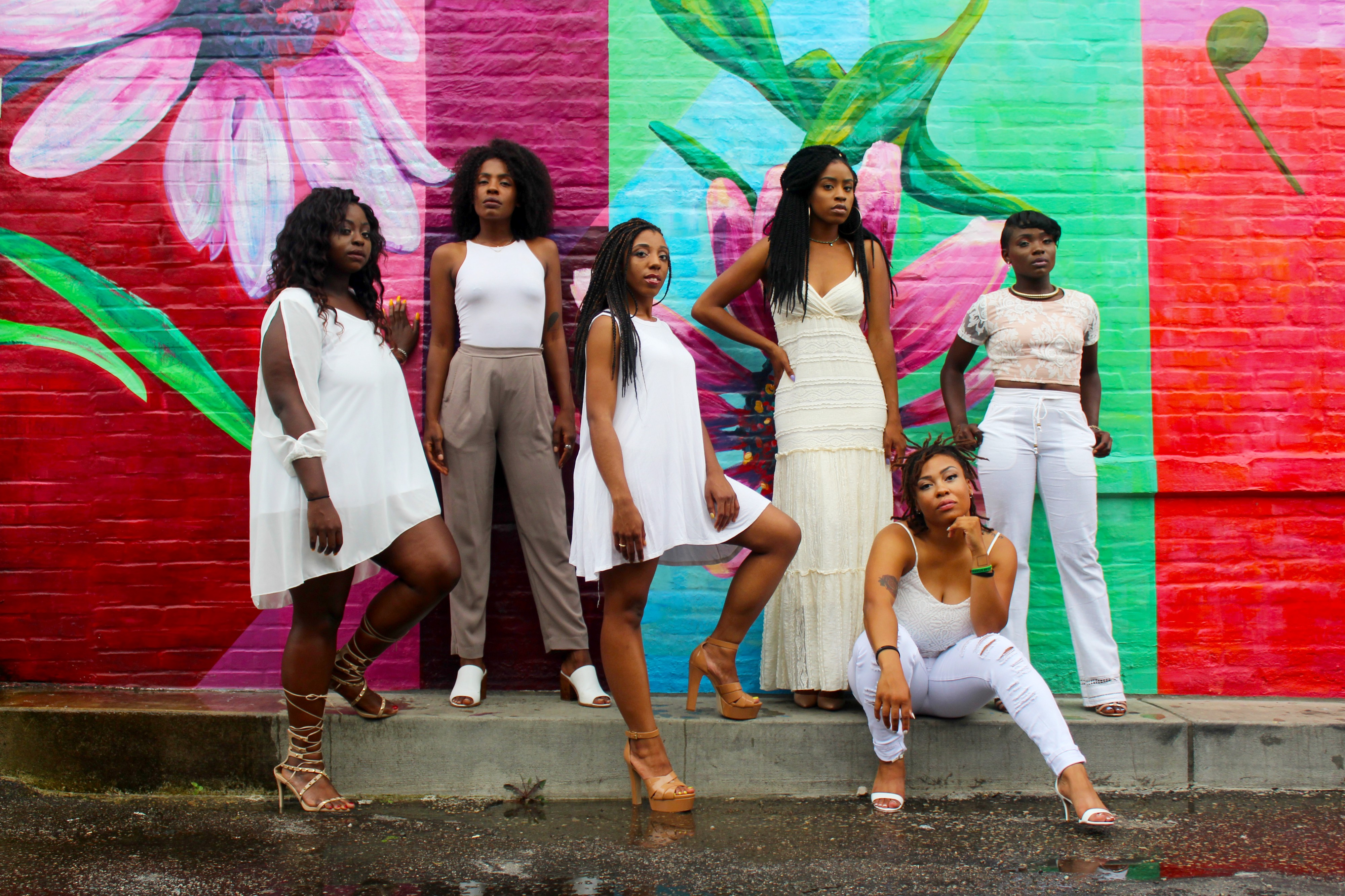 A group of African American women wearing various white outfits and posing in front of a painted wall mural.