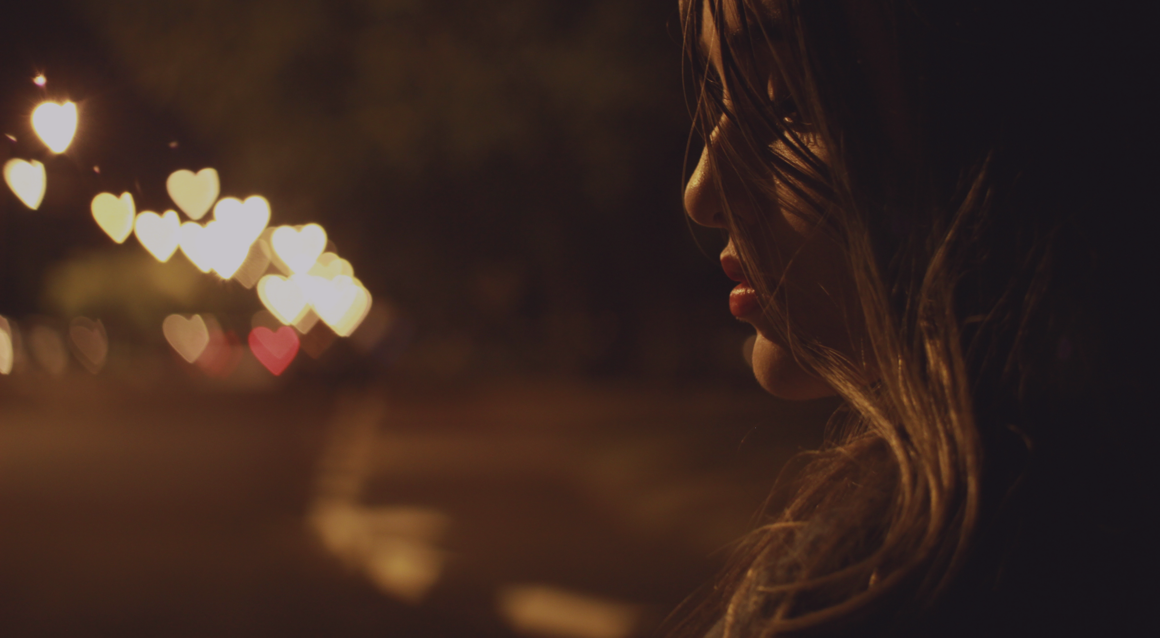 Sad woman on a city street at night, lit with heart-shaped lights.
