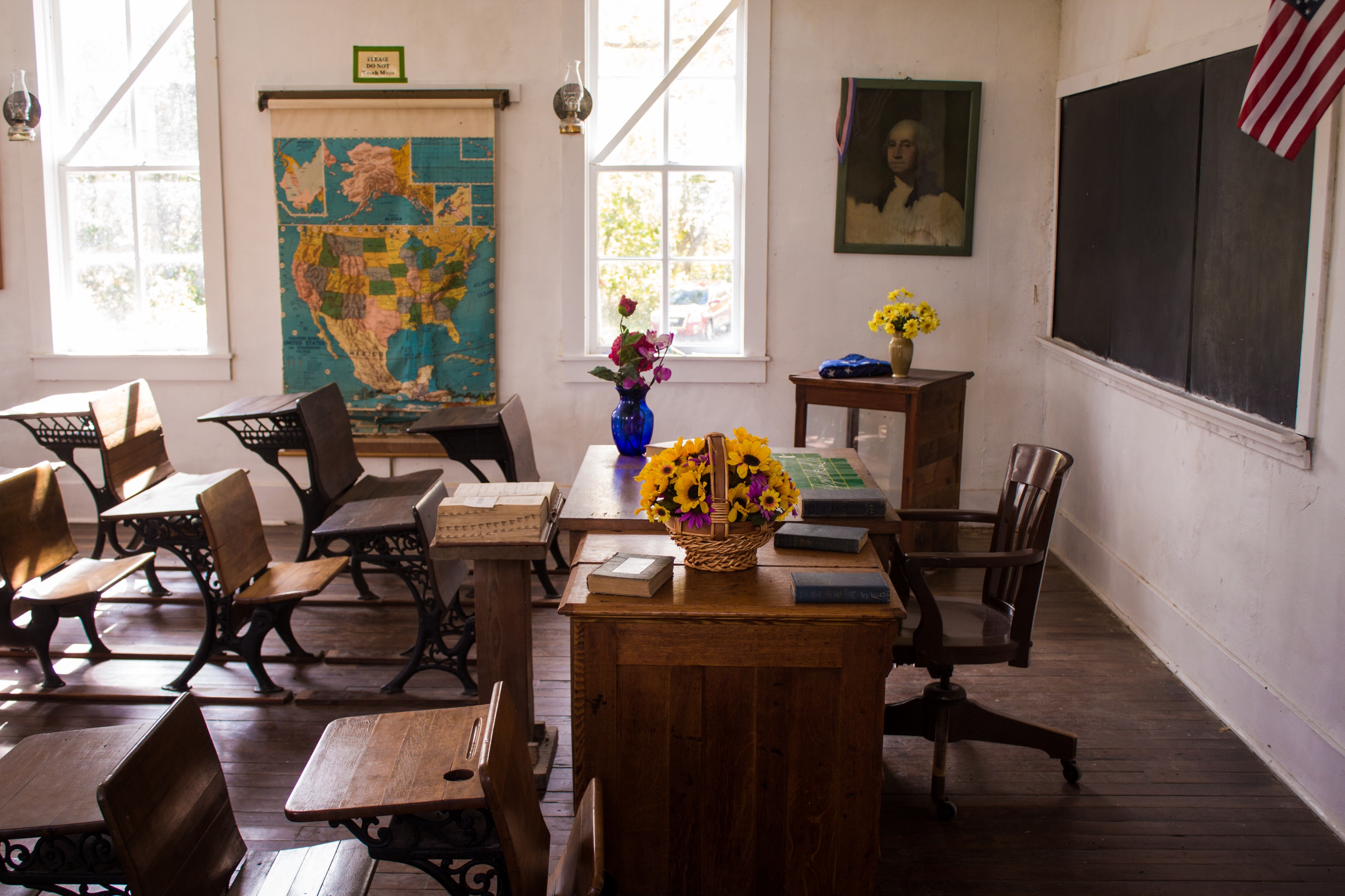 An empty classroom with wooden desks and colorful flowers on the teacher's desk.