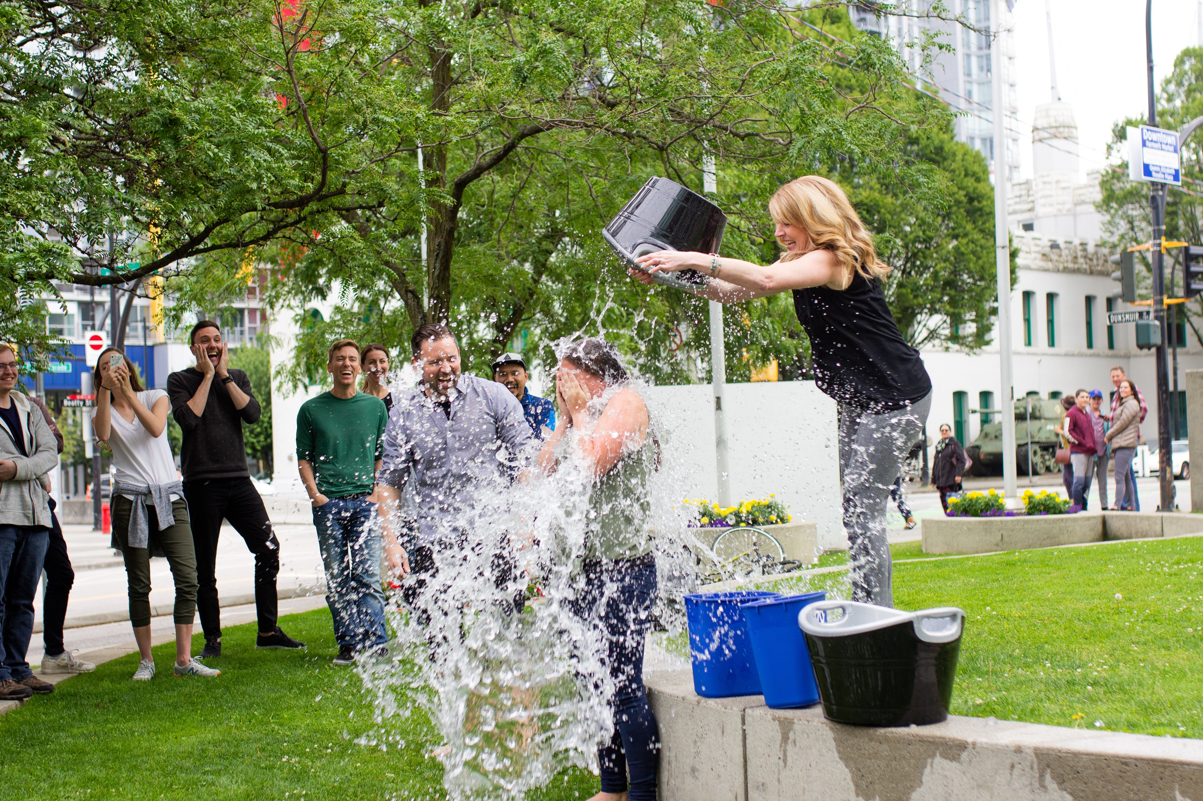 Someone getting a bucket of ice water dumped on their head to raise $$ for ALS research in a park with onlookers
