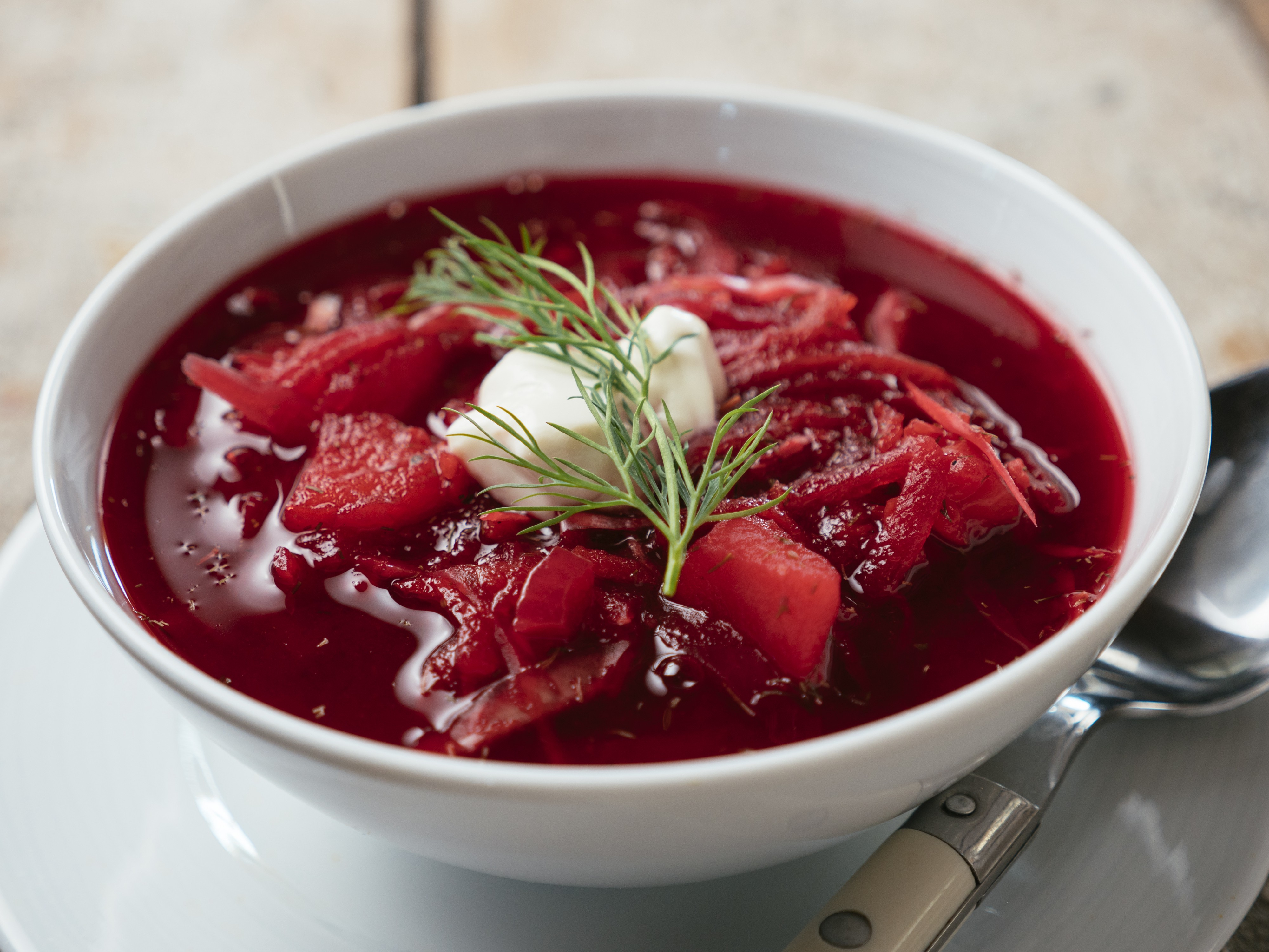 A bowl of borscht topped with a spring of dill and a dollop of sour cream.