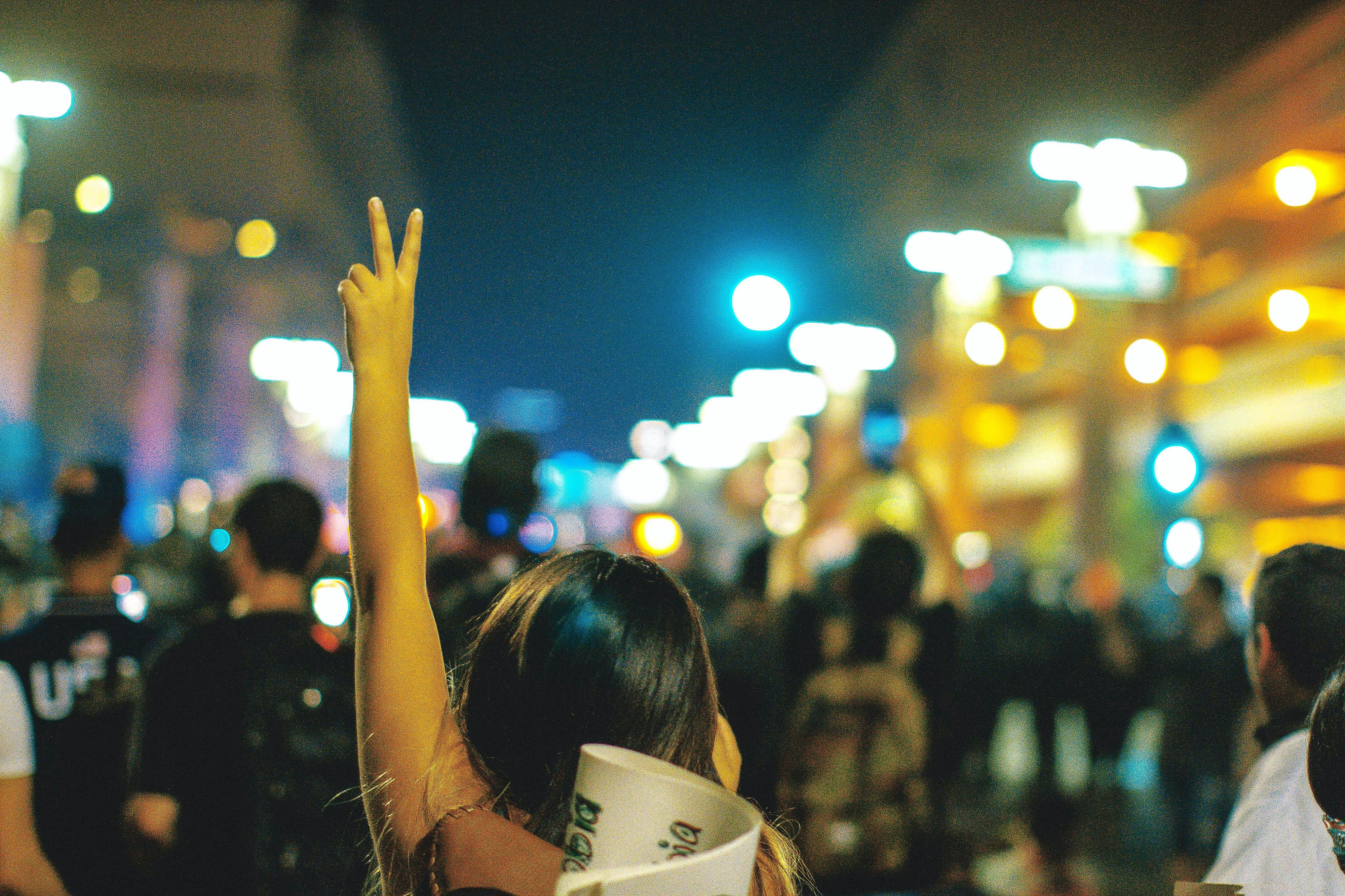 Image of a crowd with someone holding up a peace sign.