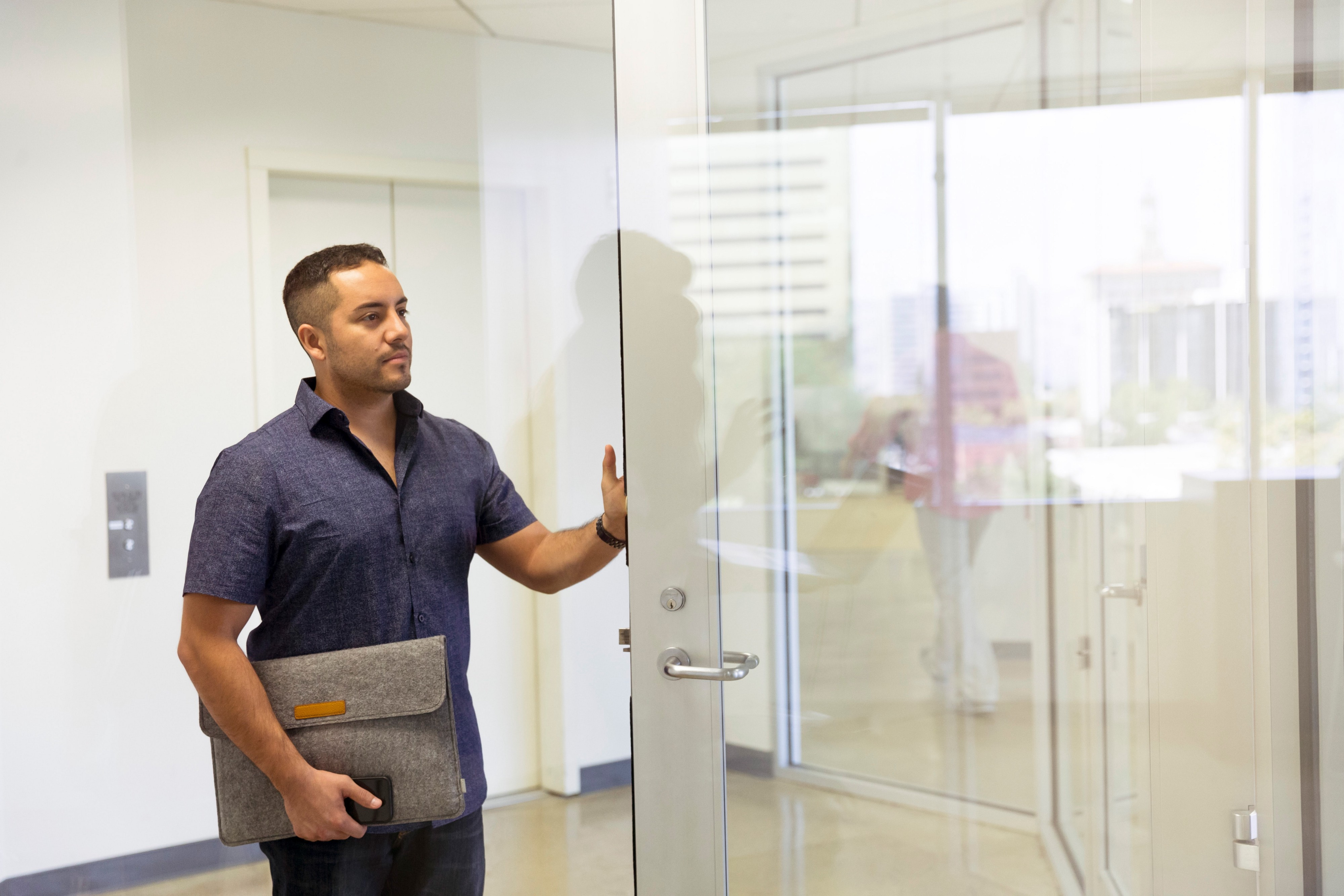 Person, dressed in a button up shirt, carrying laptop sleeve, holding a glass door open.