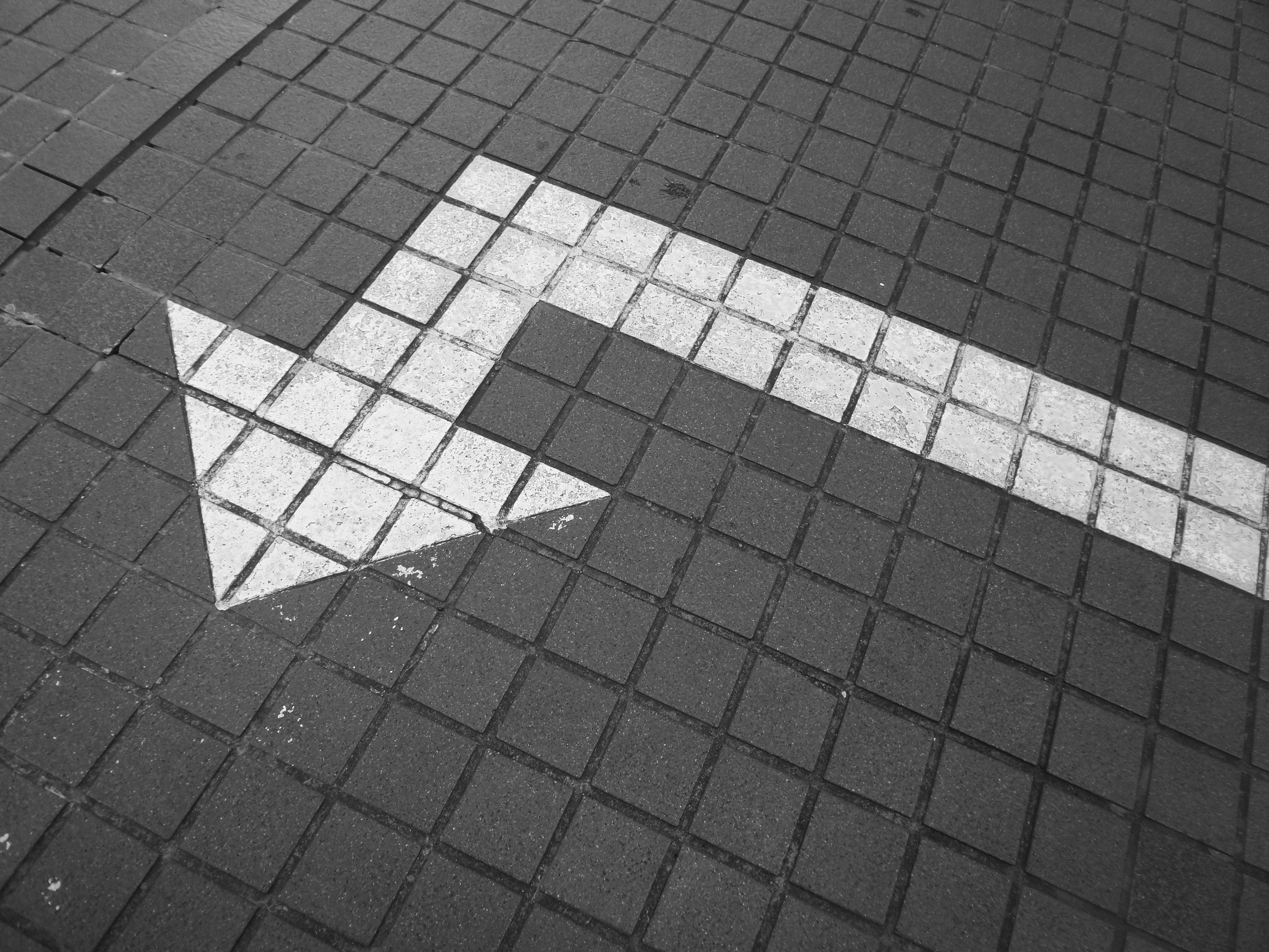 dark gray patterned floor with a white arrow pointing left