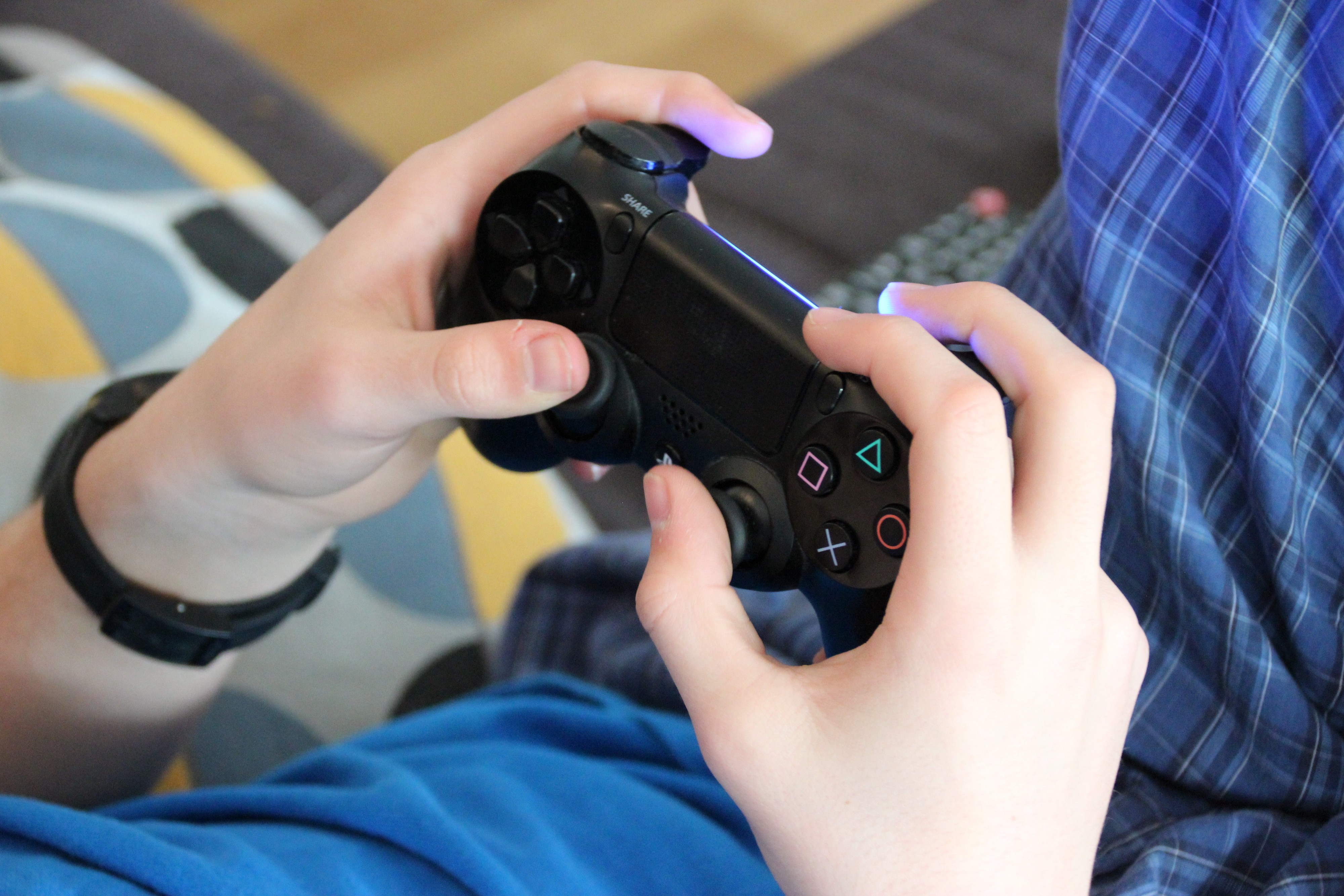 Male holding video game controller while wearing pajamas