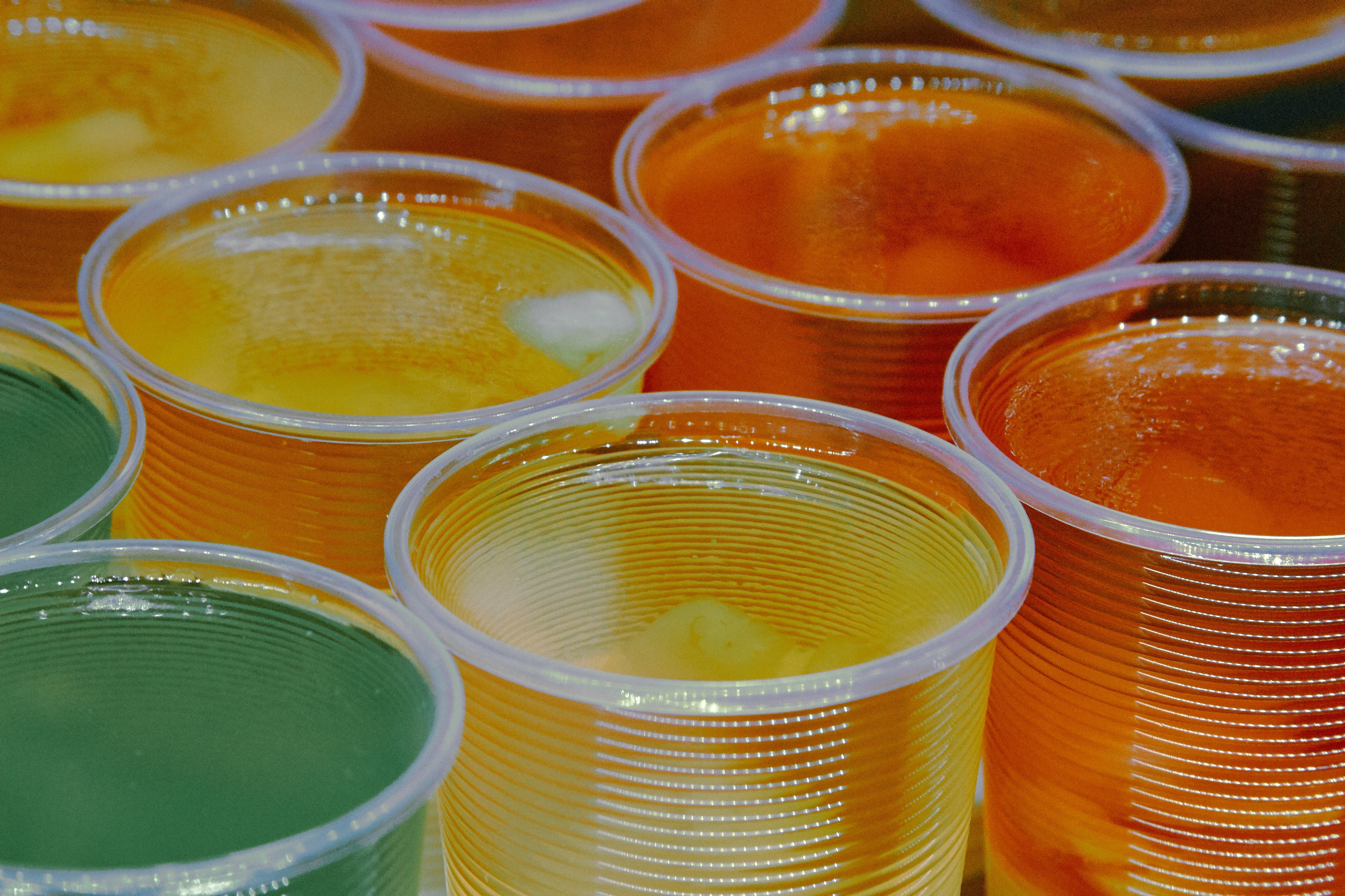 An assortment of green, yellow, and orange Jell-O shots