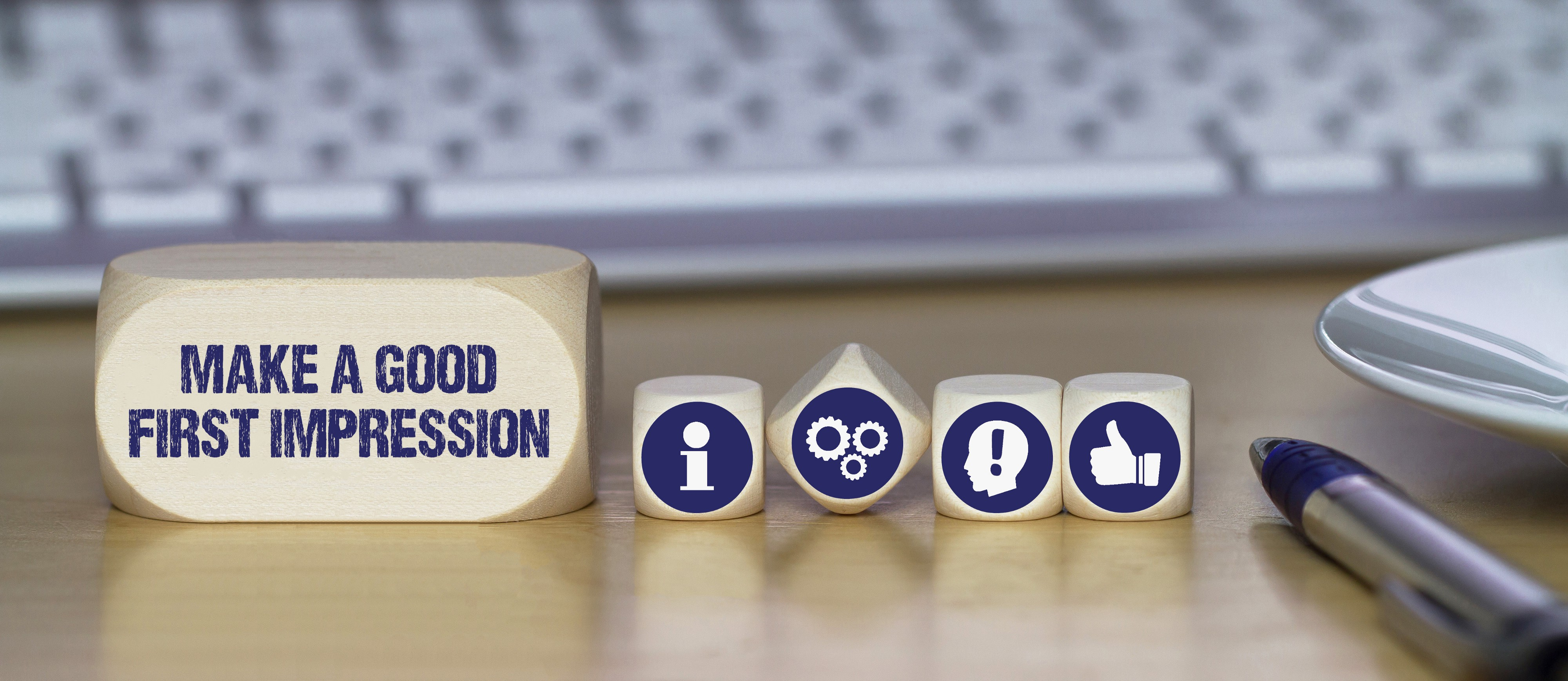 """Keyboard on desk behind social media icons on wooden cubes with the text """"make a good first impression"""" on a larger rectangle"""